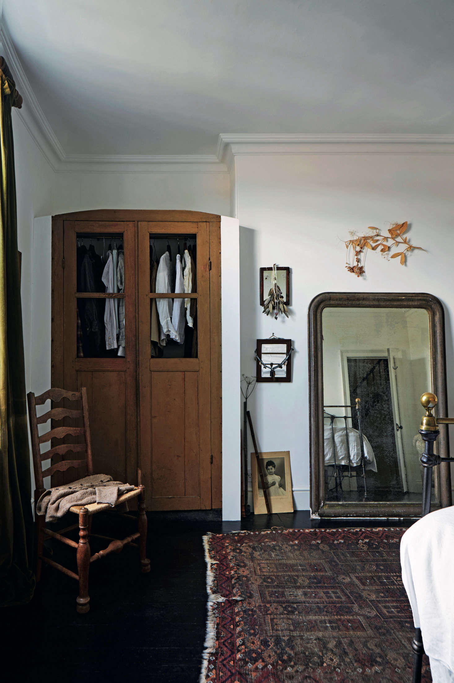 In the master bedroom, the couple inserted an antique wardrobe into a niche, and leaned a mantel mirror against the wall.