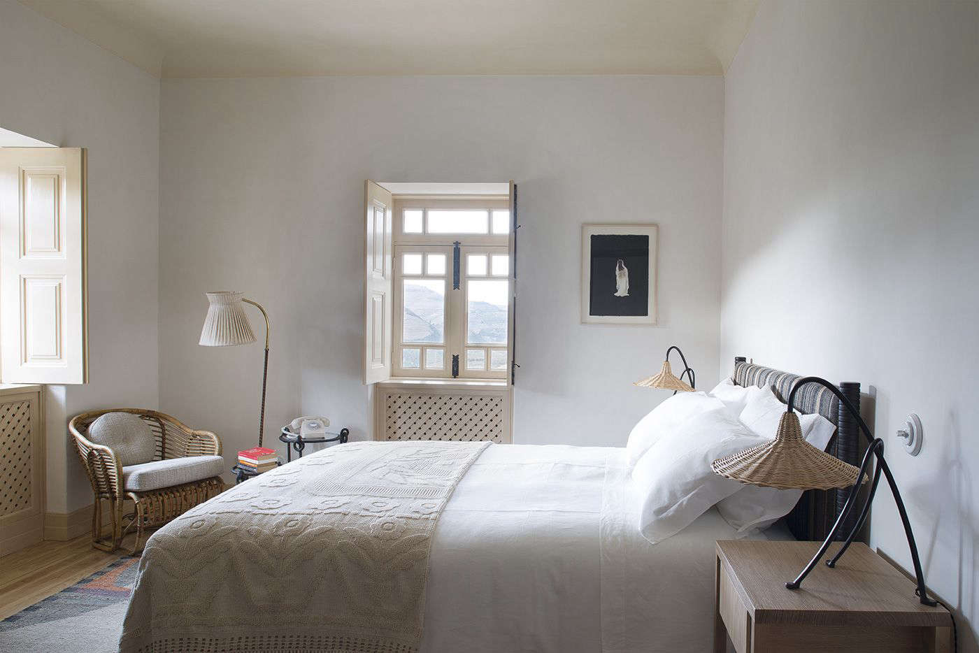 Each bedroom is fitted with rattan lamps, mix-and-match patterned blankets, and a rotary phone, an indication of the property's low-fi, off-the-grid ethos.