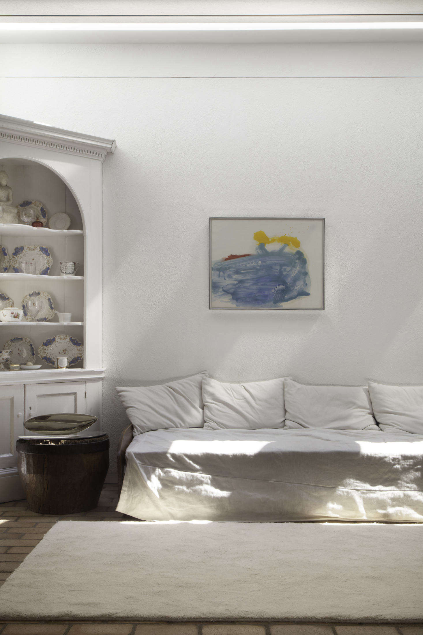 A white-painted corner hutch with blue, gold, and red china meets Helen Frankenthaler&#8