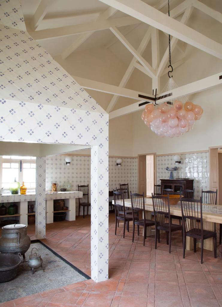In the combined kitchen and dining room, walls are tiled in traditional Portugueseazulejos.For the pale-pink glass light installation, Yovanovitch collaborated with Swiss glassmakerMatteo Gonet.