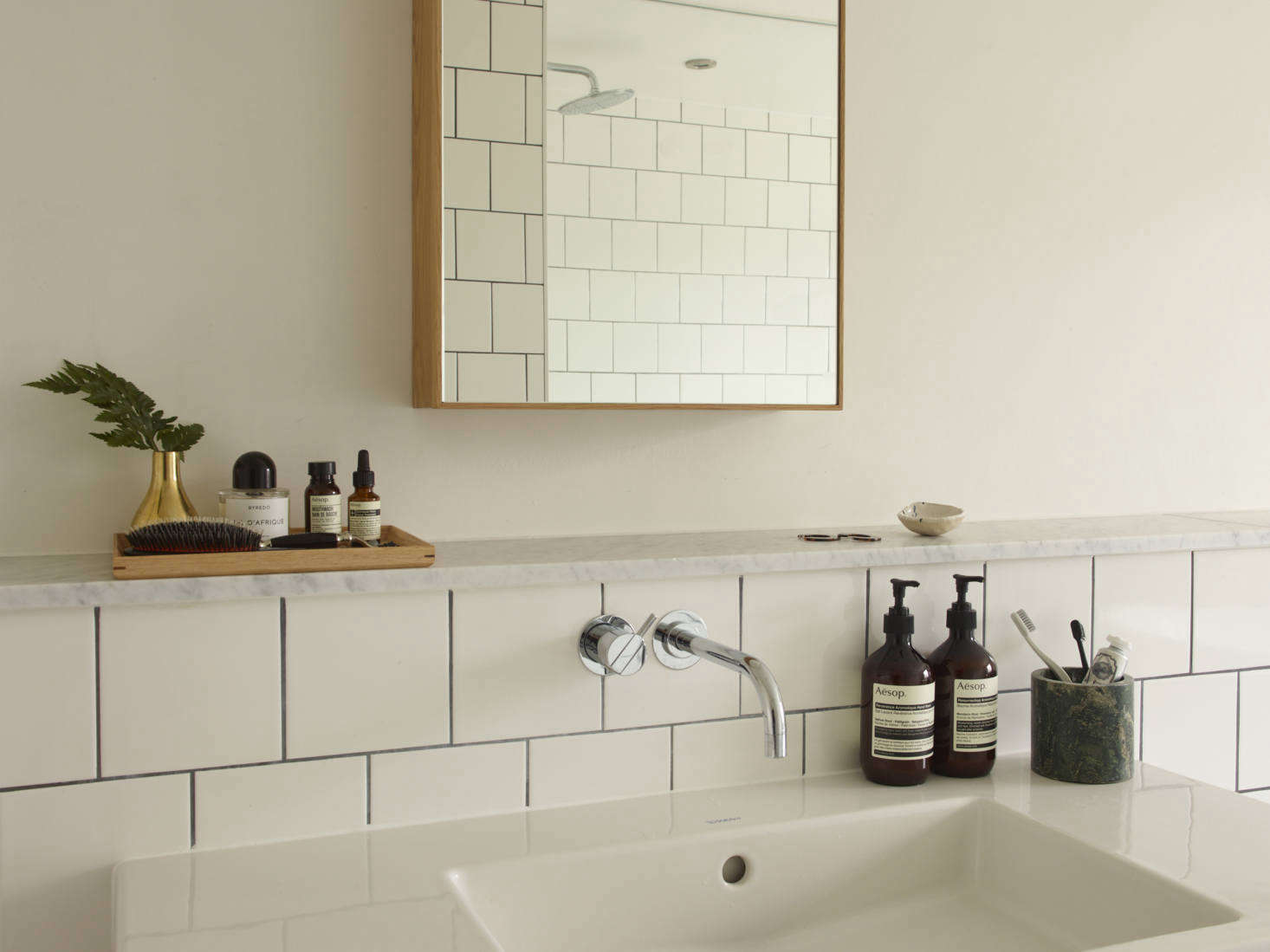 A marble shelf above the sink is a place for contained skincare products and brushes. Photograph by Richard Round-Turner fromA Star Is Born: A Rehabbed London Maisonette from a Newly Minted Designer, High/Low Secrets Included.