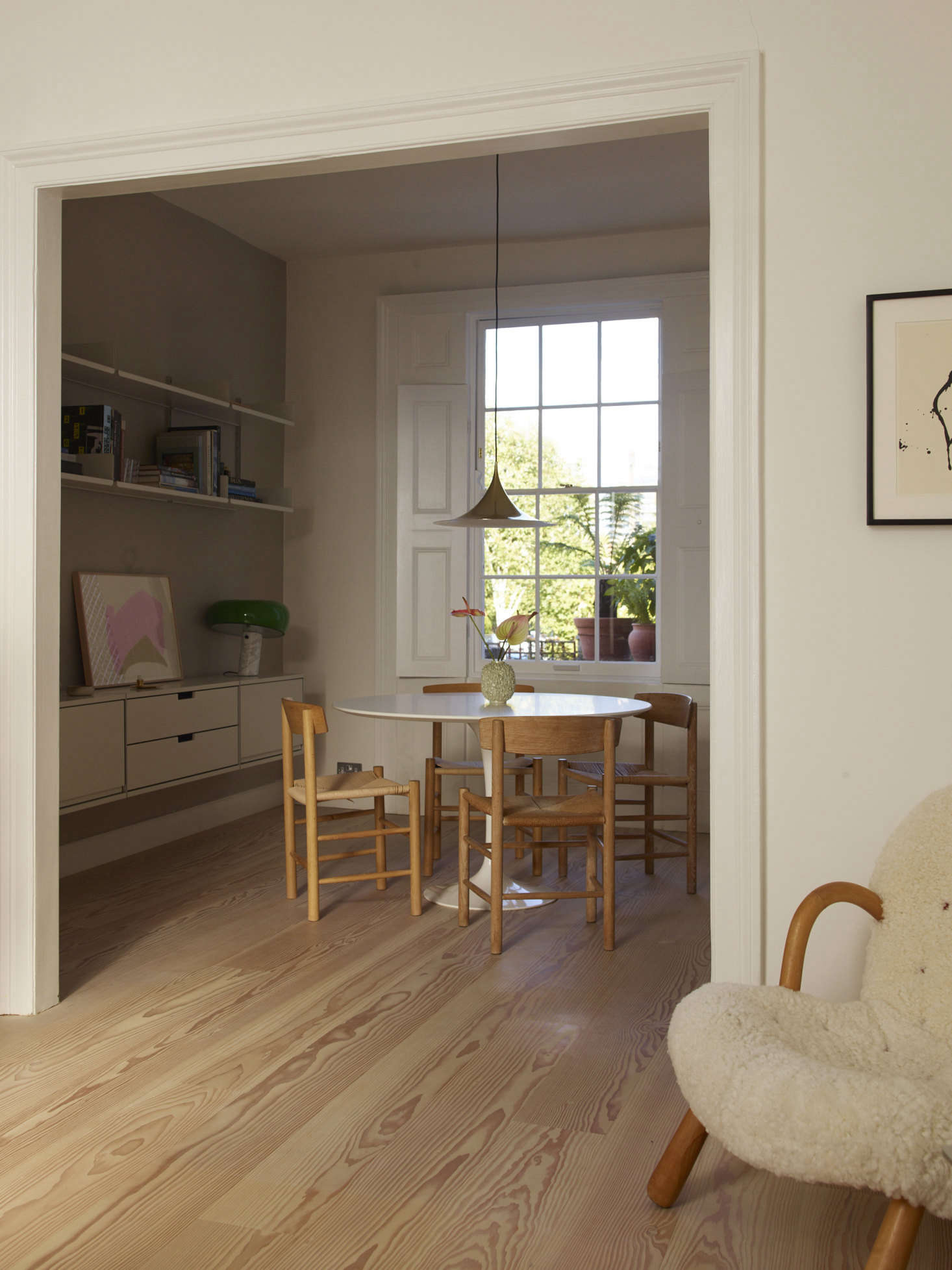 The dining room, with a Vitsoe wall-mounted shelving unit and a vintage Gubi pendant from Denmark.