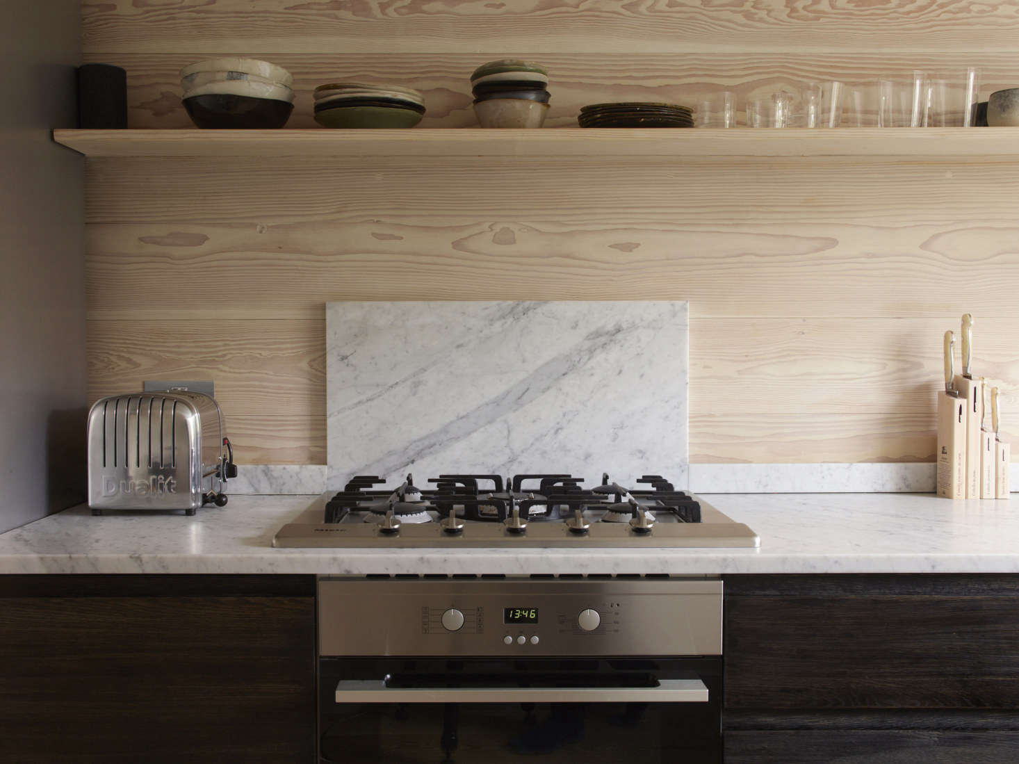 The couple resourcefully used leftover Dinesen boards to clad one wall of the kitchen. A slab of marble forms a minimalist backsplash.