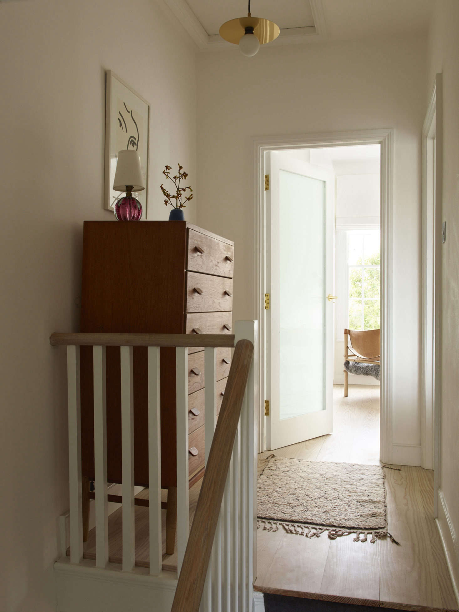 At the top of the stairs: a hanging pendant by Atelier Areti and, on the dresser, a pink Murano glass lamp from Etsy.