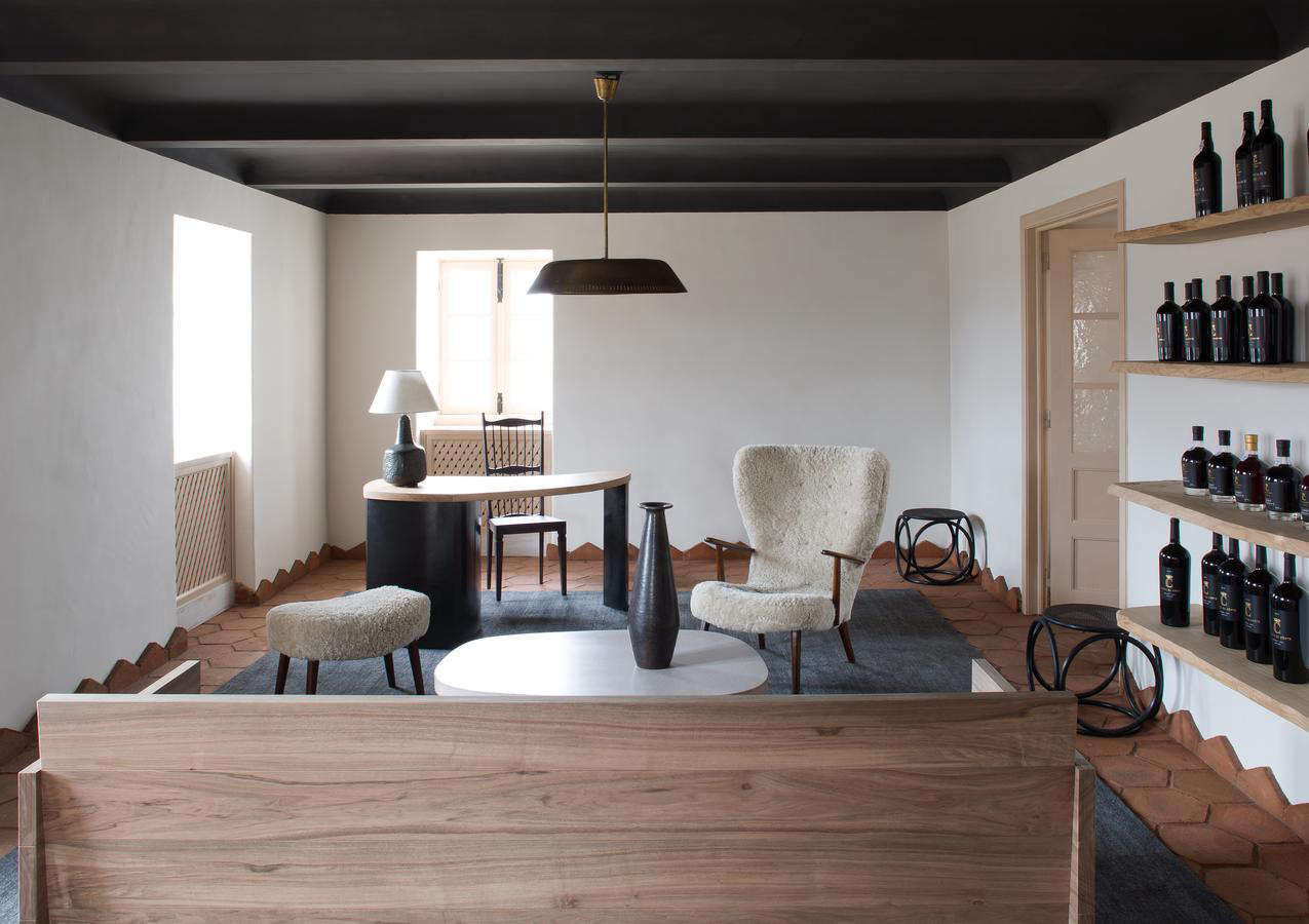 Another living space in a cohesive color palette, with a black-painted ceiling and black rug. The sheepskin chair is Yovanovitch's own design, and on the shelves are the winery's own bottles.Note how the floor tiles continue up the walls, into a geometric baseboard of sorts.