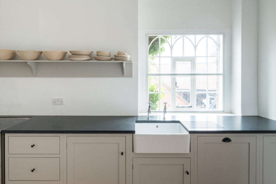 Streamlined under-counter cabinets from deVOL, a slate countertop with integrated dish drainer, and a single wall-mounted shelf, all along one wall, make up the kitchen.