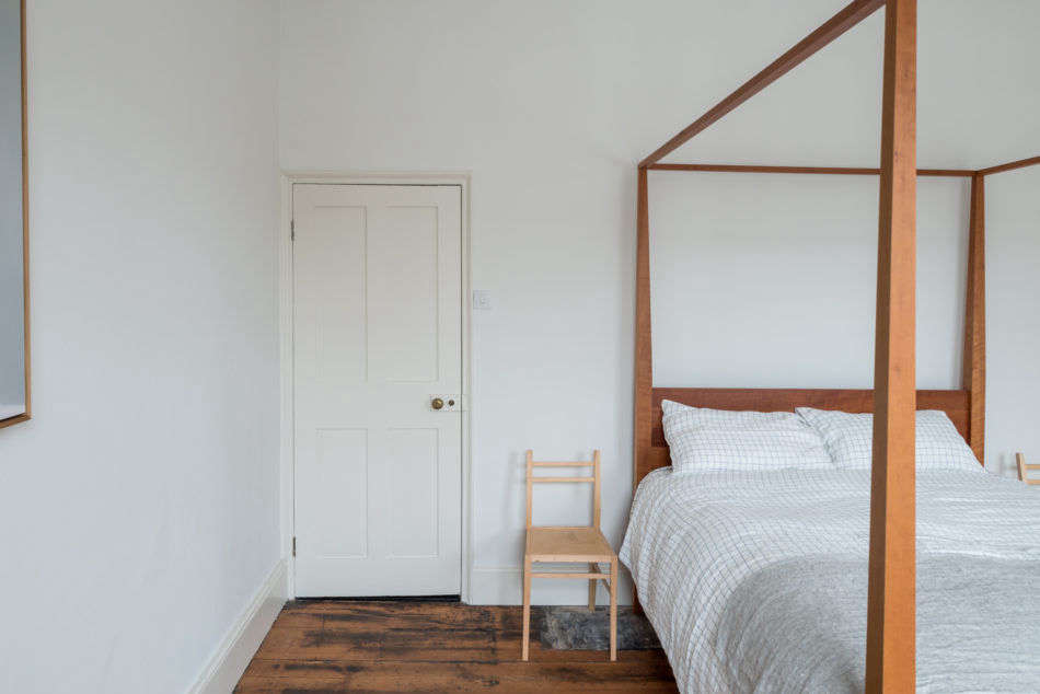 Just off the kitchen is the bedroom. Here, a canopy bed is flanked by two hazel-wood chairs by Sebastian Cox.