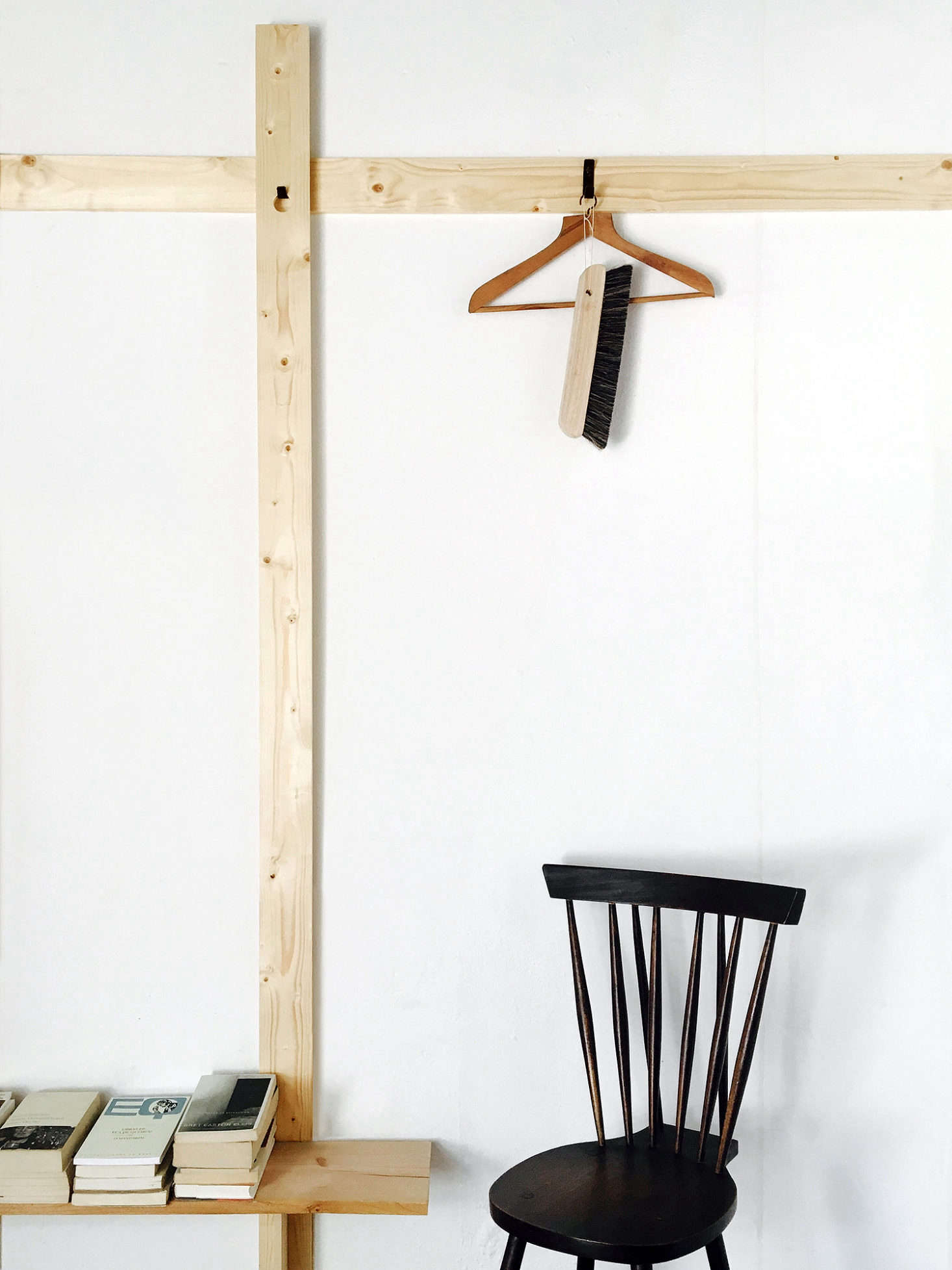 Removable black hooks turn the simple lengths of wood into storage.