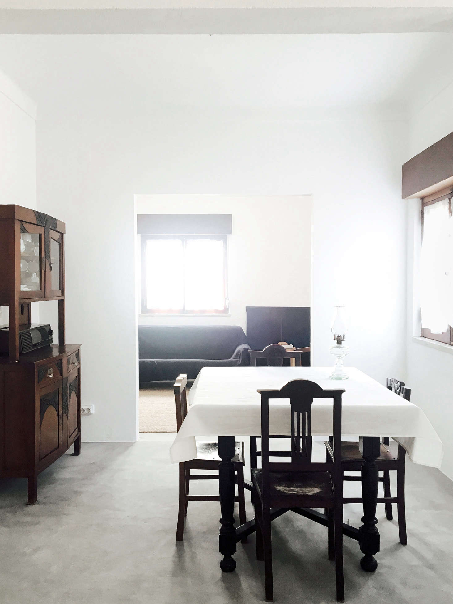 """The dining area and living room beyond. """"Doors and windows were preserved with their original varnish finishing and hardware from the 1970s,"""" Bento says. All of the furniture was existing in the house, including the wood hutch and dining chairs, both """"believed to be from the 1960s,"""" Bento says."""