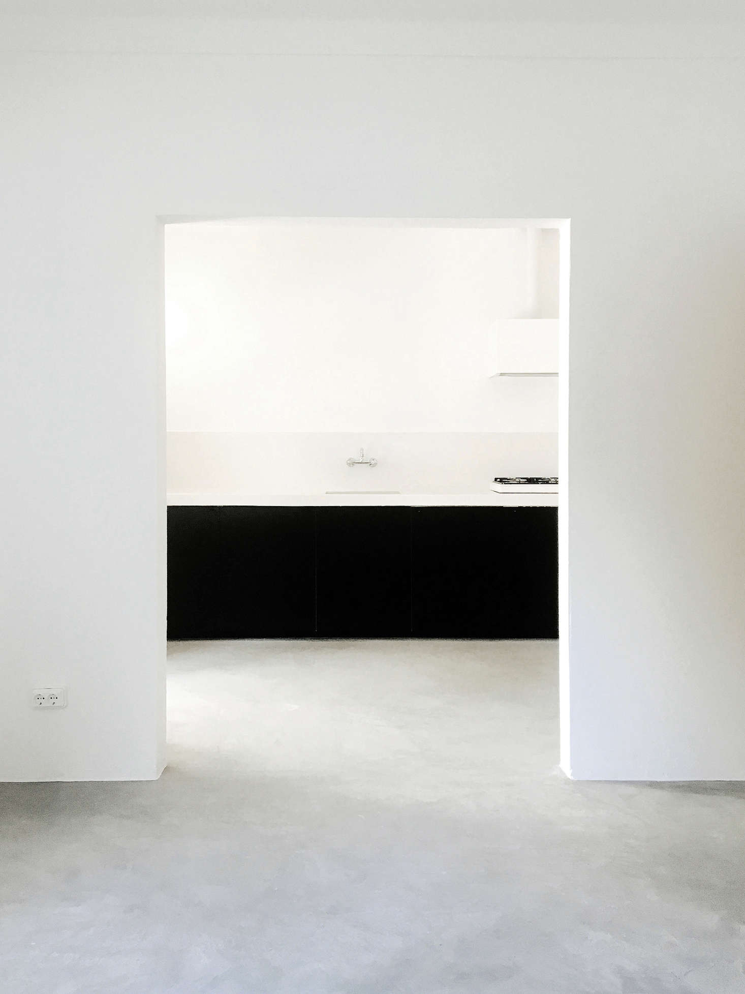 A lesson in sparseness: A wide, sculptural doorway leads into the kitchen. Because the interiors are so spartan, Bento chose the limited materials with care: white-washed plaster walls and matte concrete floors that have a subtle visual texture.