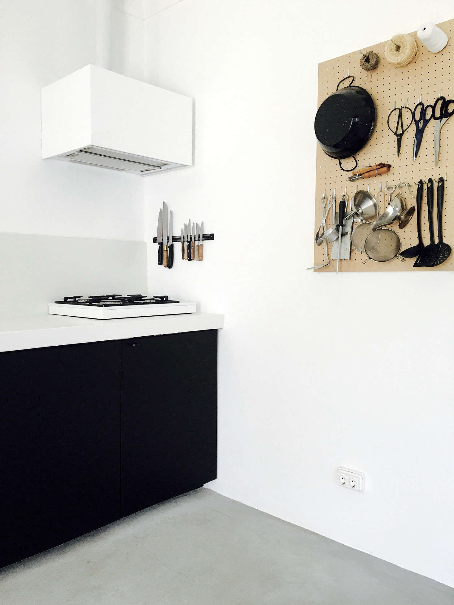 By the small gas cooktop is a well-appointed pegboard, which holds kitchen shears and even a silver pitcher.