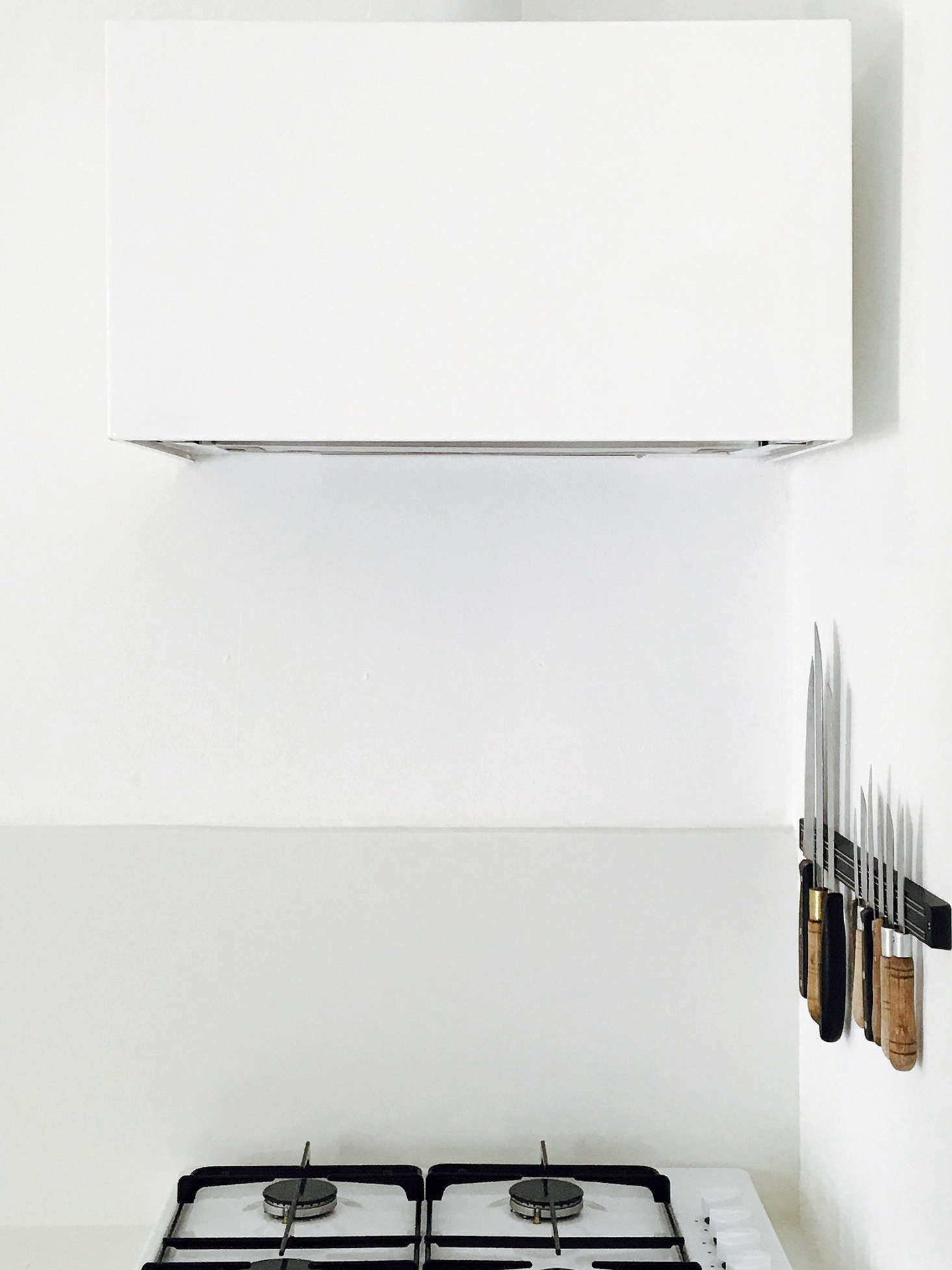 In an otherwise austere kitchen, necessary storage doubles as design, as in the knife rack beside the cooktop. The sculptural vent hood cover and the base for the range are both made of thin steel, painted with primer and matte white paint, and made by a local metalworker.