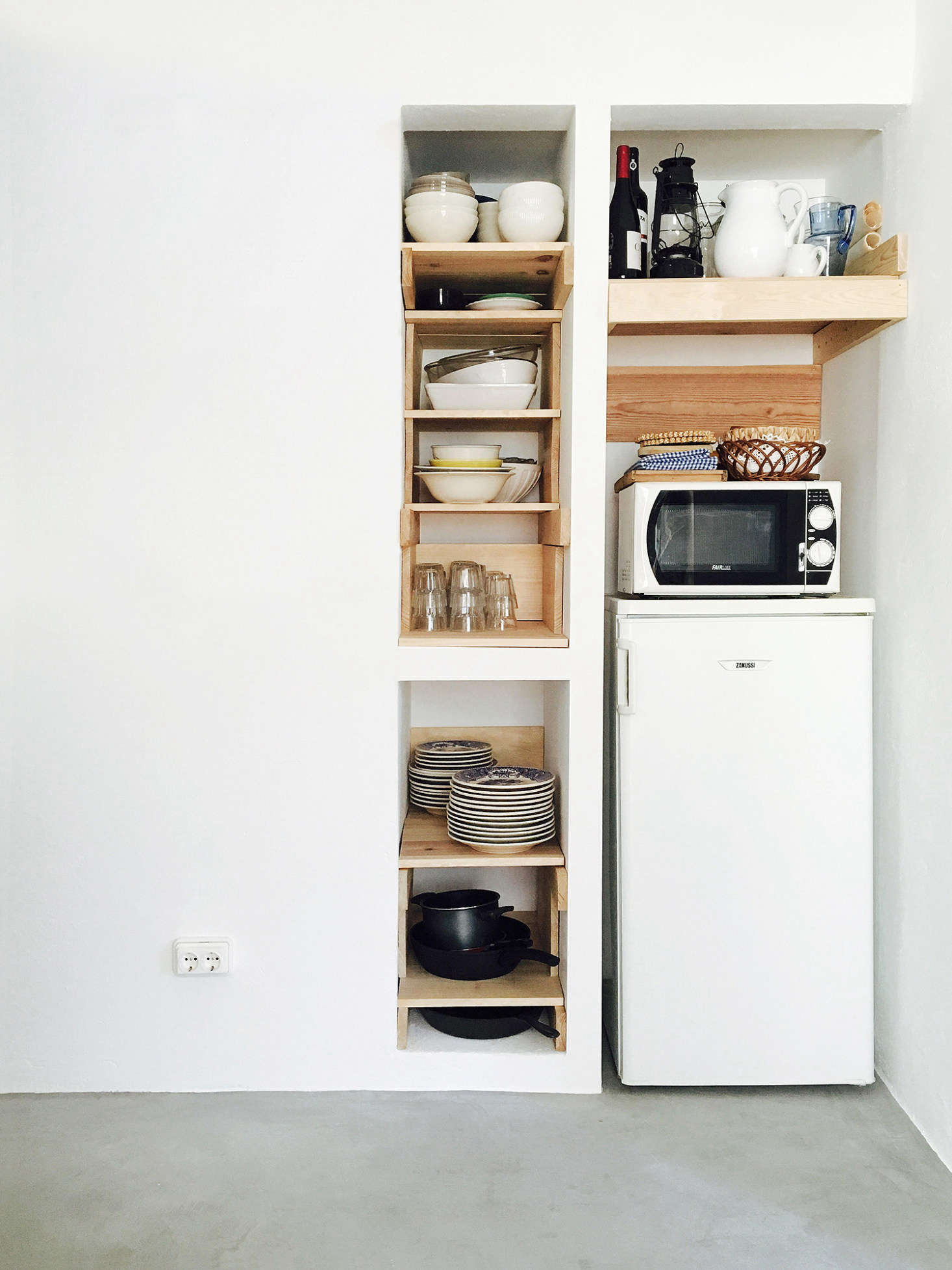 Bento chose waxed woodwork as a third main material, and it's a theme repeated throughout the house. Here, it forms ad-hoc open storage in a niche beside the European-sized refrigerator.