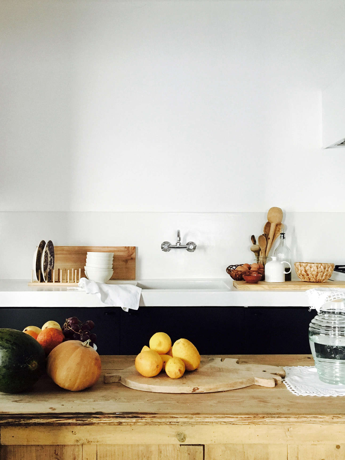 """The kitchen, with poured-in-place concrete countertops and backsplash (""""single pour,"""" Bento says) and a rough-hewn wooden island."""
