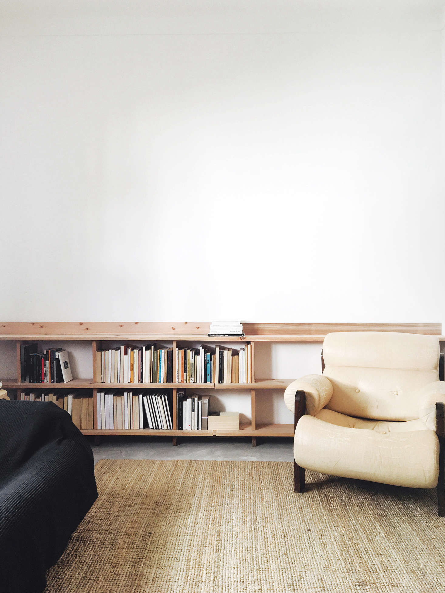 In the living area, attention is focused on the lower half of the room, with a simple woven mat and a low, waxed-wood bookshelf built into one wall.