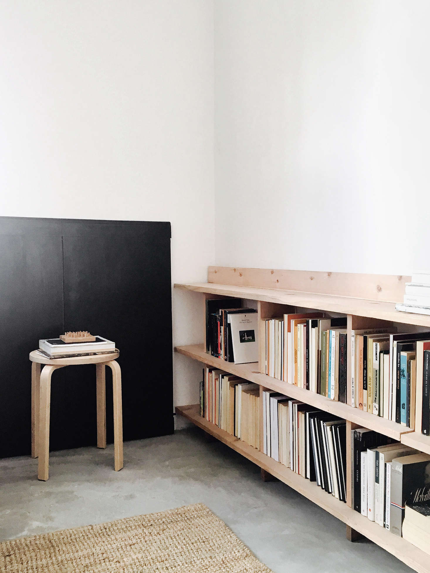 """In one corner, an Alvar Aalto lookalike stool serves as an end table. Against the wall is an extension for the dining table that doubles as""""vague wainscoting."""""""
