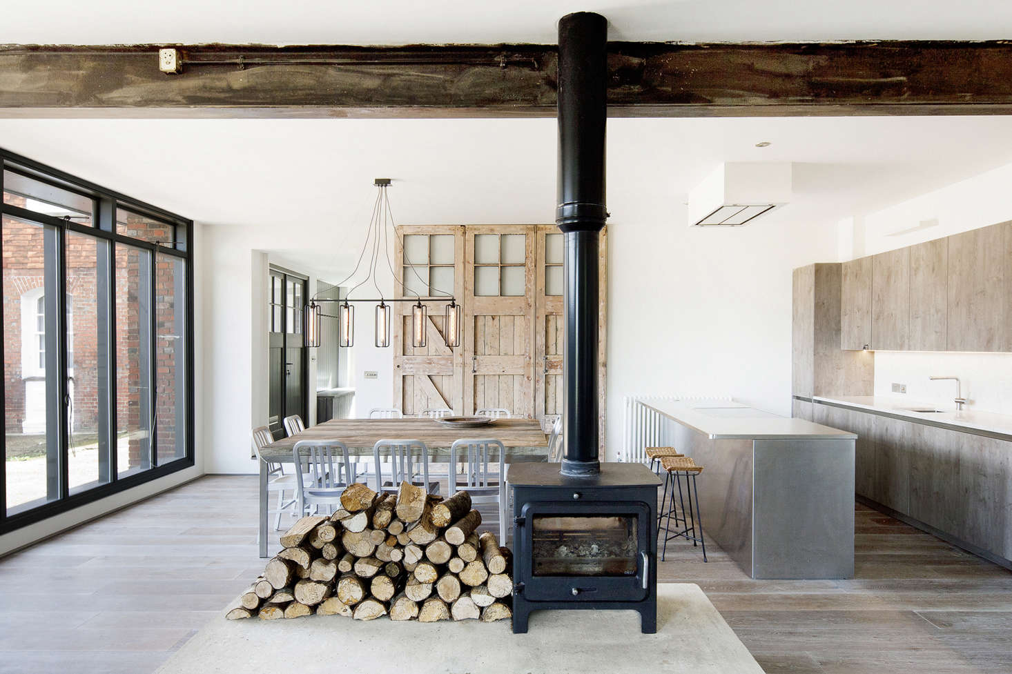 Inside, a double-sided wood-burning stove stands on a large concrete plinth in the middle of the space, creating a central heat source and focal point. Medieval dwellings were often arranged around a central hearth, and Nowicka sees this is a nod to the far-reaching history of the area.