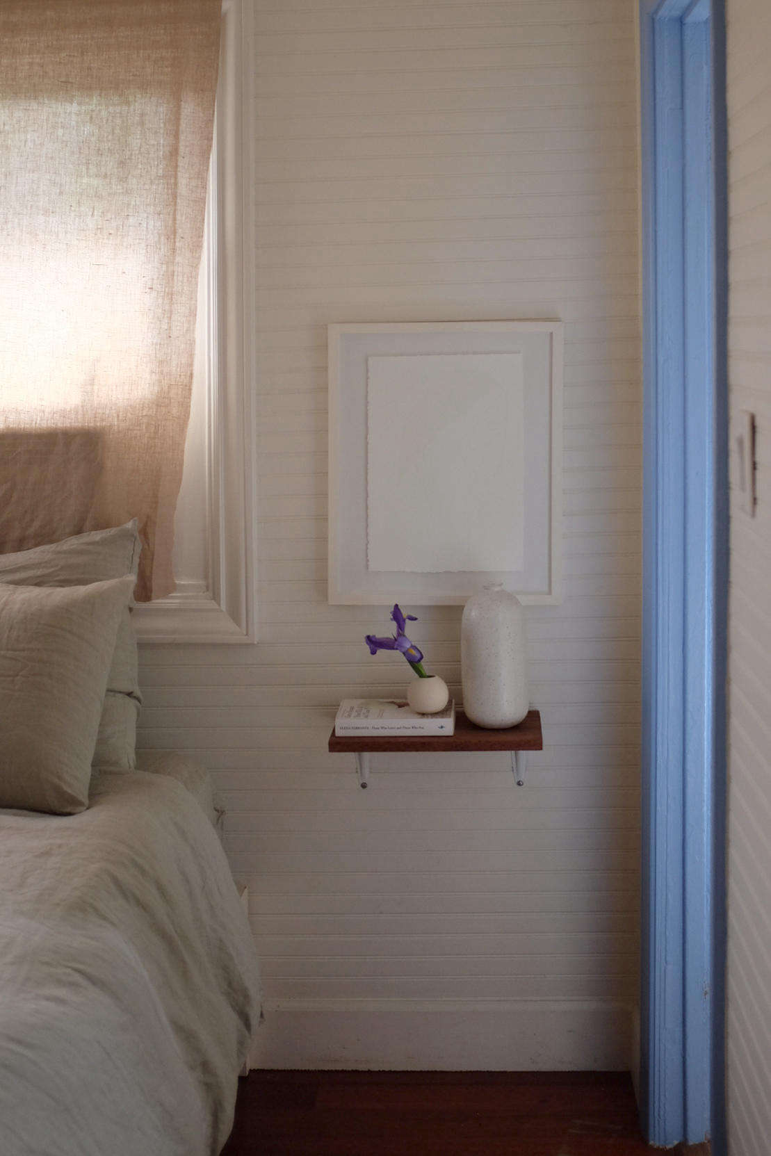 To save space, Alex and Jodi used small shelves in place of nightstands. The bed frame is from Ikea.