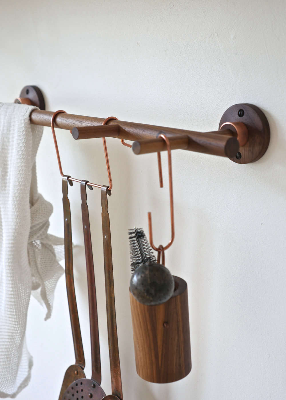 The Dowel Rail, also shown in walnut and copper, has pegs, and can be hung with Turiello&#8