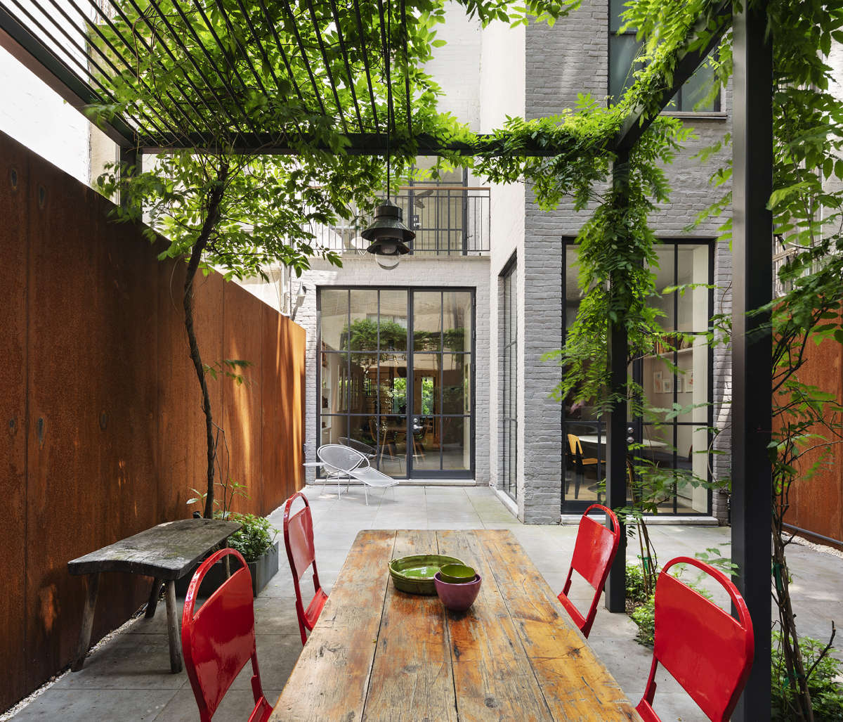 """""""We essentially built the garden around the wisteria,"""" O'Neill says, of the tree on the left. It's the only plant they kept from the original backyard. The walls are made from sheets of corten steel, the same type of metal favored by artist Richard Serra. """"Sam likes the way it weathers."""""""