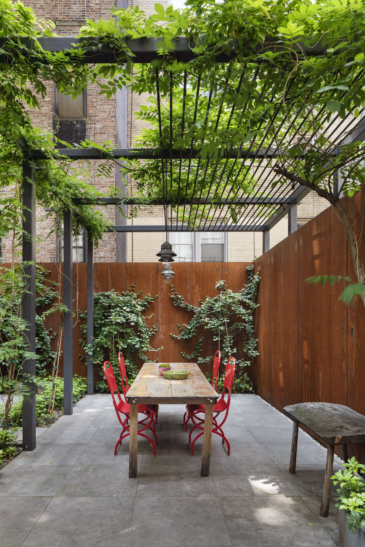 The outdoor space is anchored by a custom steel trellis.