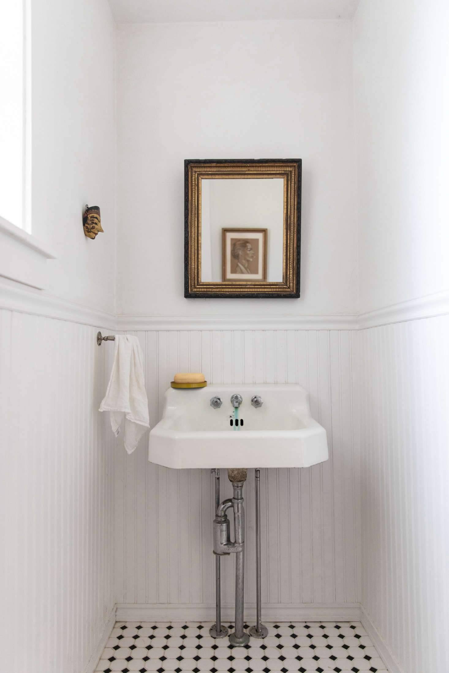 """One of two bathrooms, with beadboard wainscoting and a well-loved sink. """"The mask is Balinese, brought back by a friend—it oddly looks very much like him,"""" McNeil says. """"The portrait I loved because she's so determined and yet so beautiful. It's a pastel from the 1950s, found in an antique store in Camden."""" The antique gold-and-black mirror is from a shop in Belfast."""