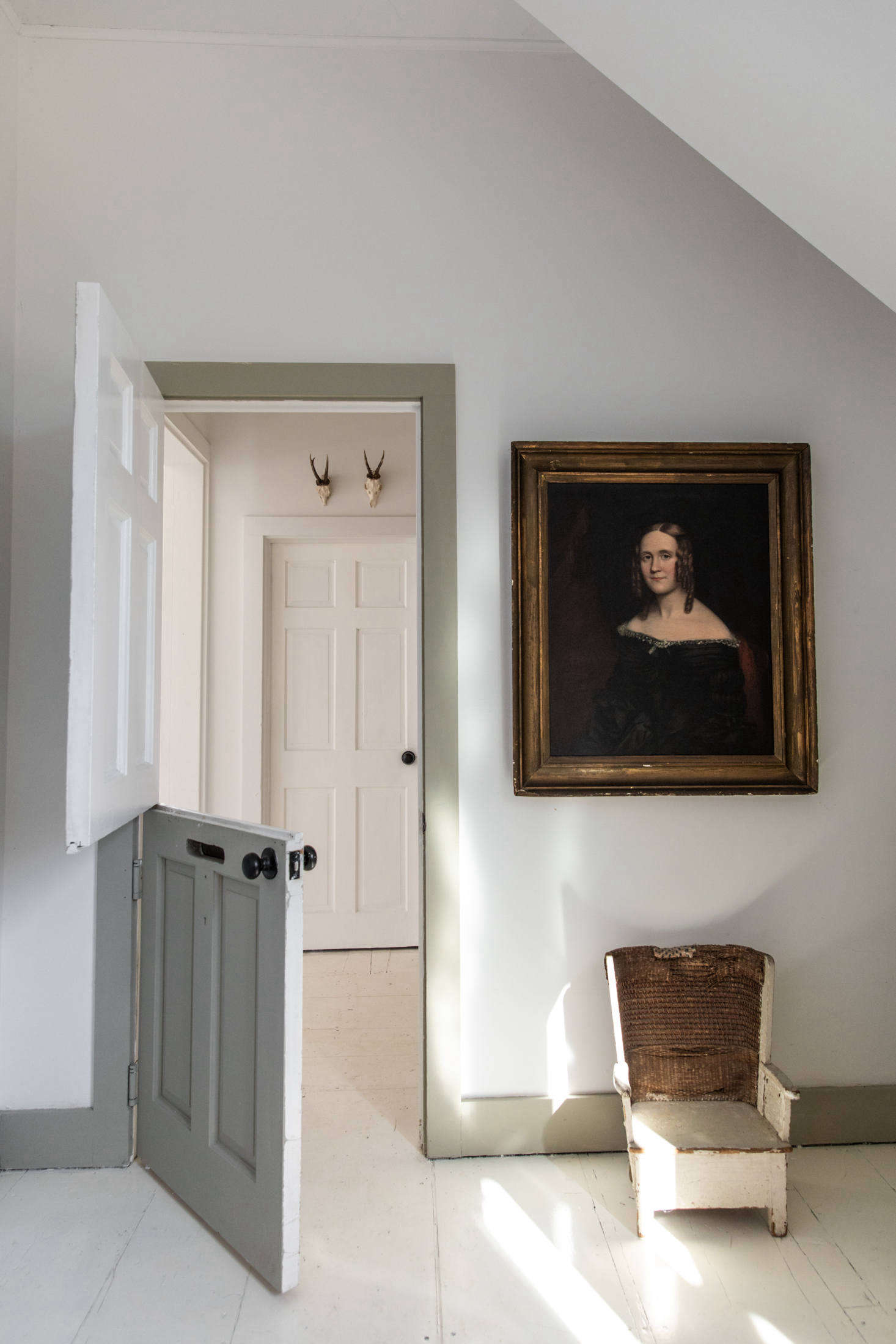 Just off of the entryway, a Dutch door leads to a small bedroom, the first of four.