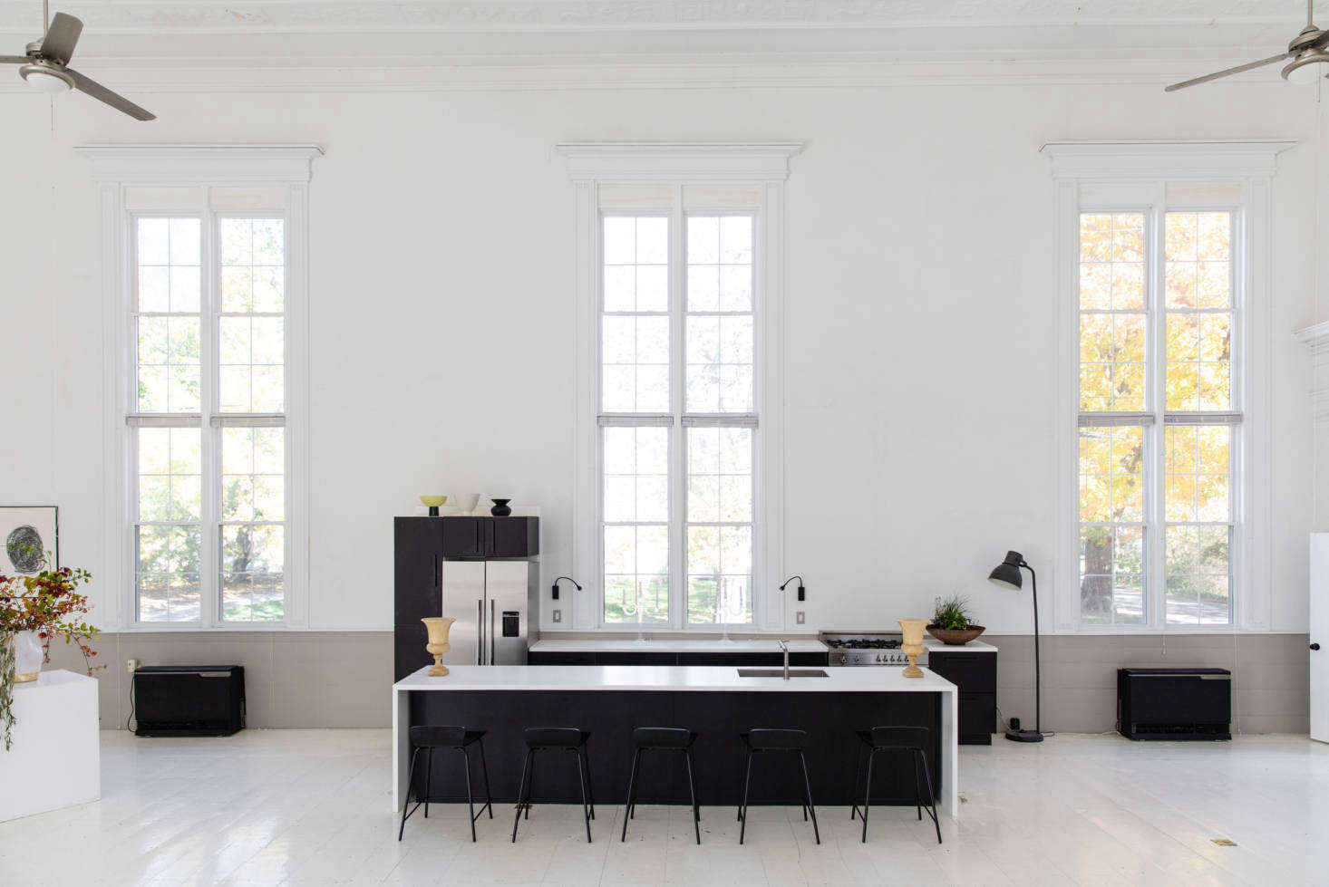 """McNeil installed a kitchen in the center of the main space, framed by the windows. Though it looks like a high-end kitchen system, it's actually black Ikea cabinetry with countertops from Lowe's. """"I wanted it to convert easily to a ' bar' for the public events,"""" McNeil says."""