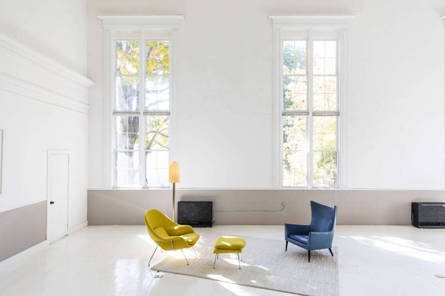 """The deconstructed living area is set apart by a rug, and fitted with an Eero Saarinen Womb Chair (""""reupholstered in vintage Knoll fabric to retain authenticity,"""" McNeil says) and a vintage blue Danish chair. The wonky floor lamp is an Italian Murano glass design from the 1950s."""