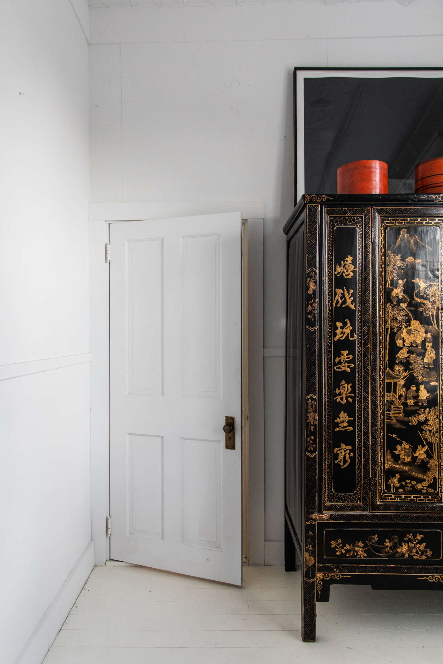At the foot of the bed is a black lacquer Chinese armoire that McNeil found in Lincolnville. &#8
