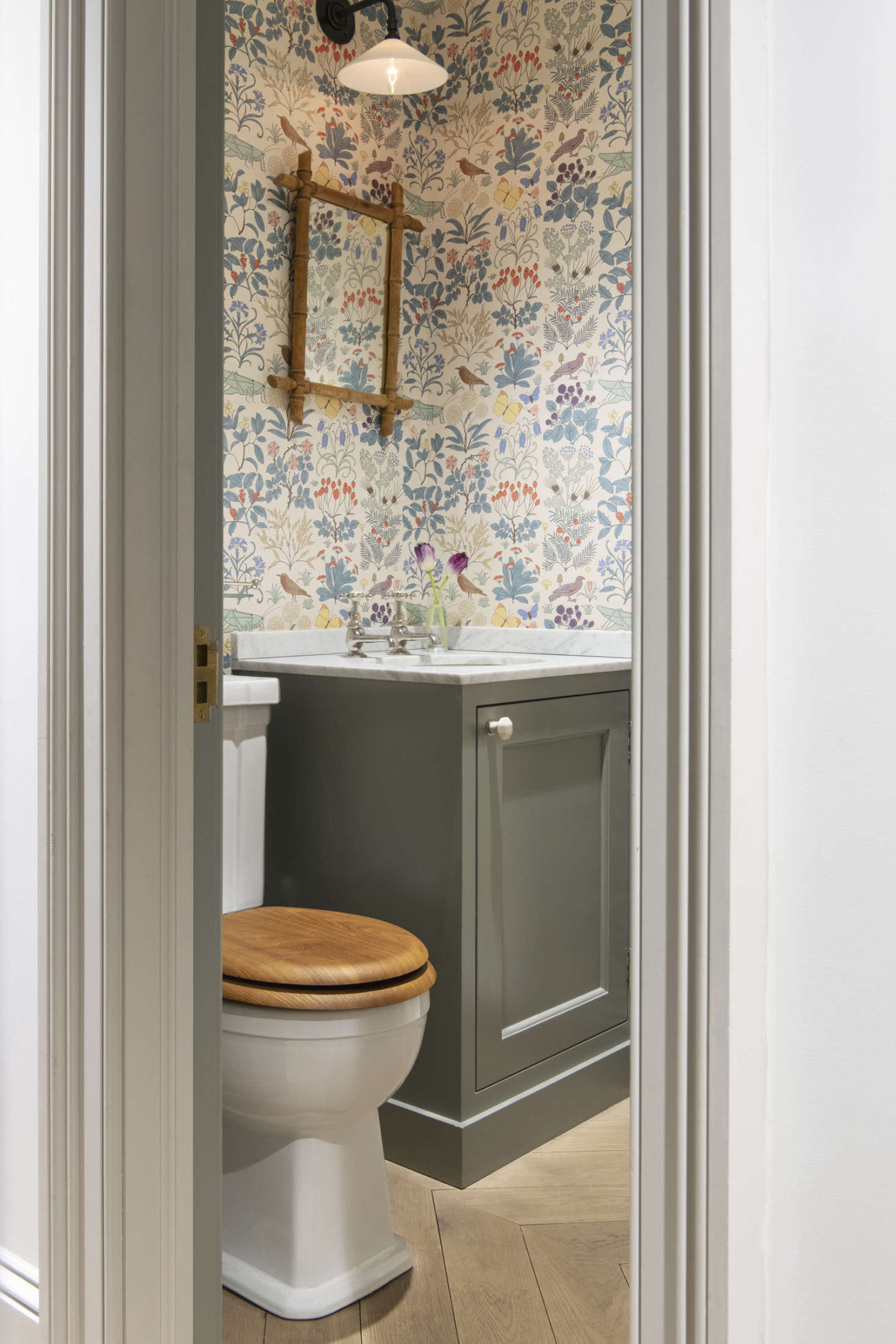The powder room is papered in CFA Voysey's 1926 pattern Apothecary's Garden from Trustworth Studios. (See the same pattern in a Jersey Ice Cream Co. country house bedroom.) The sconce over the mirror is the Glass Wall Light from Hector Finch.