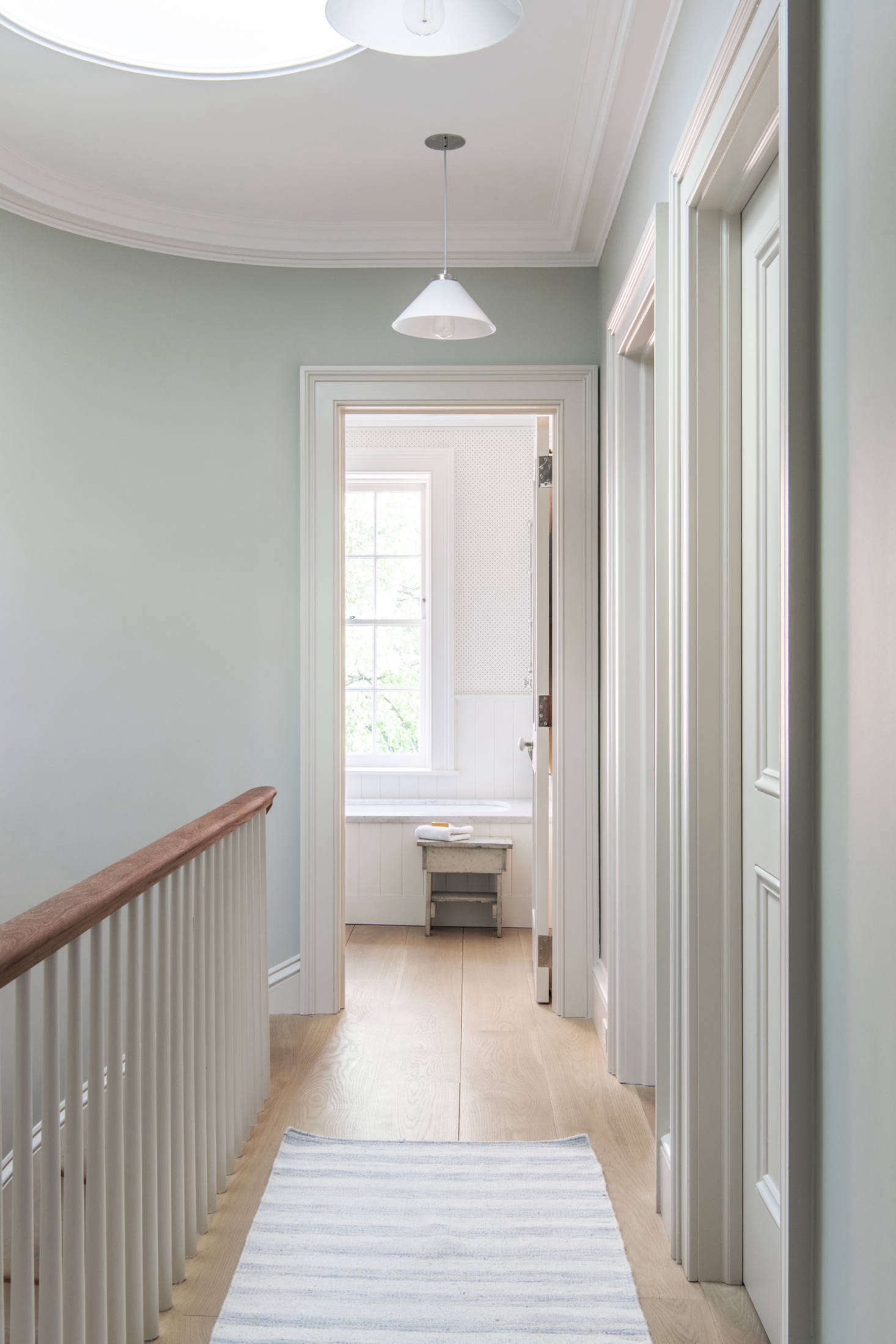 The skylit top floor is the children's quarters. The mahogany handrail is original and the rest is a replica. The walls are painted Cromarty and the trim is Shadow White, both from Farrow & Ball.