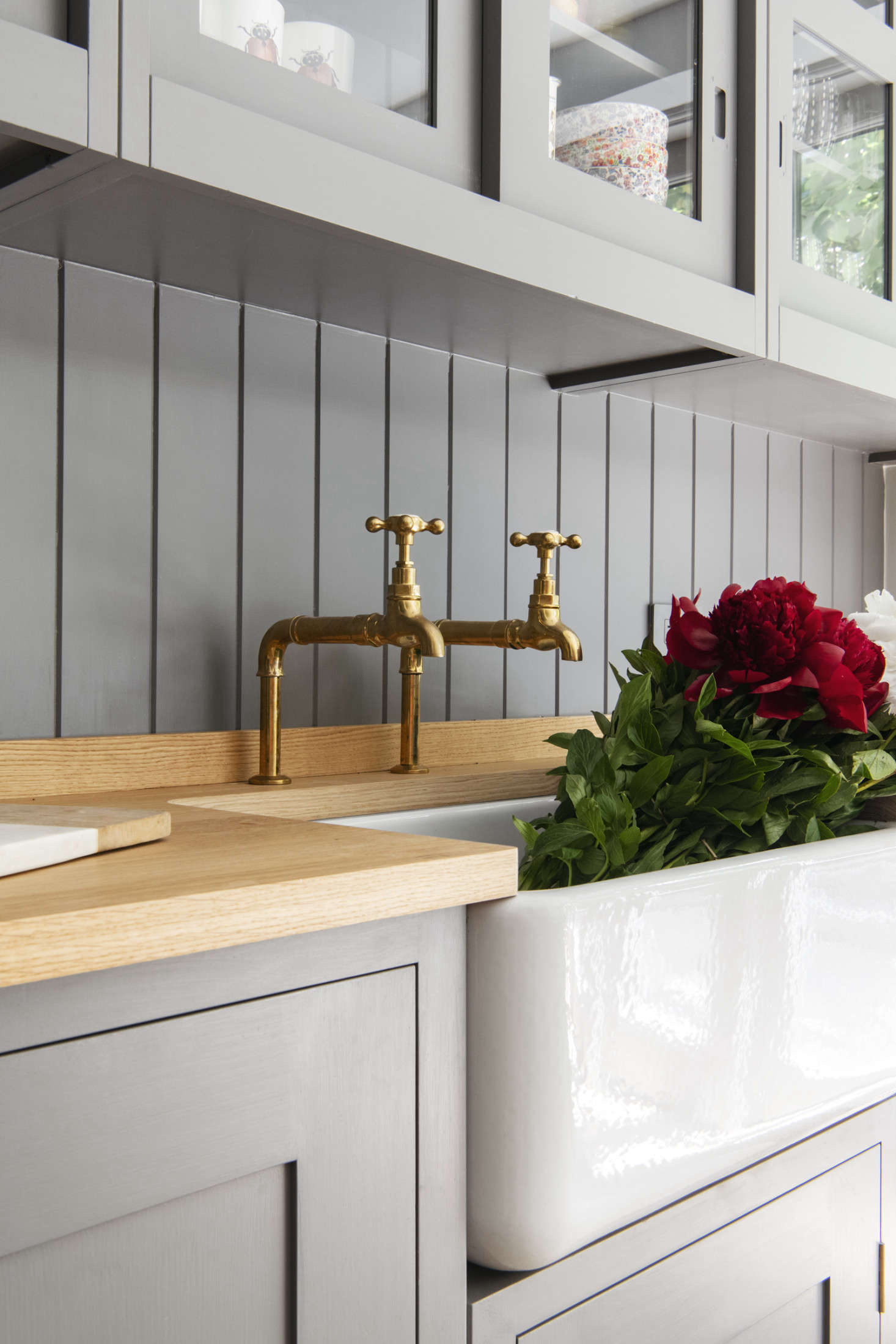 Barber Wilsons hot and cold taps in unlacquered brass and a Shaws Original farmhouse sink. The counter is Plain English oak butcher block.