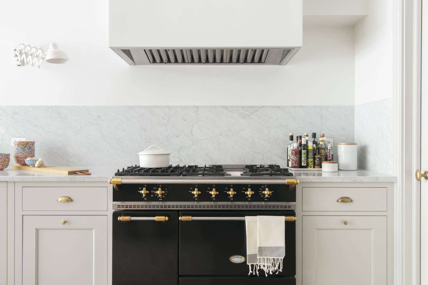 The range is La Canche's Saulieu Classique in matte black. The pull-out cabinets on either side of it hold pots and pans.