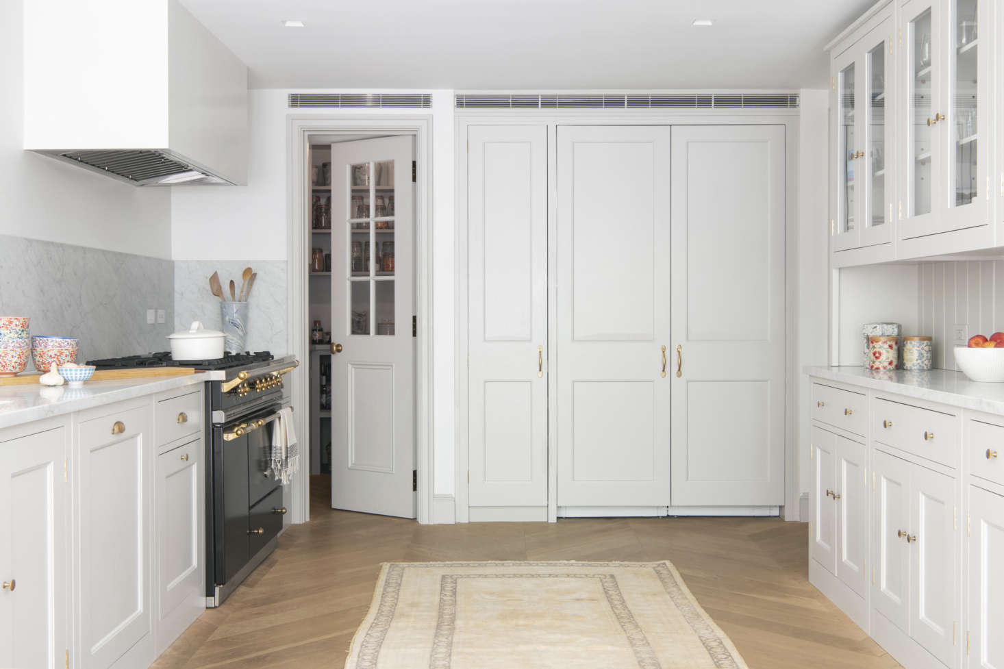An integrated Sub Zero double-doored fridge in the back of the room is flanked by a pantry on one side and the mudroom on the other.