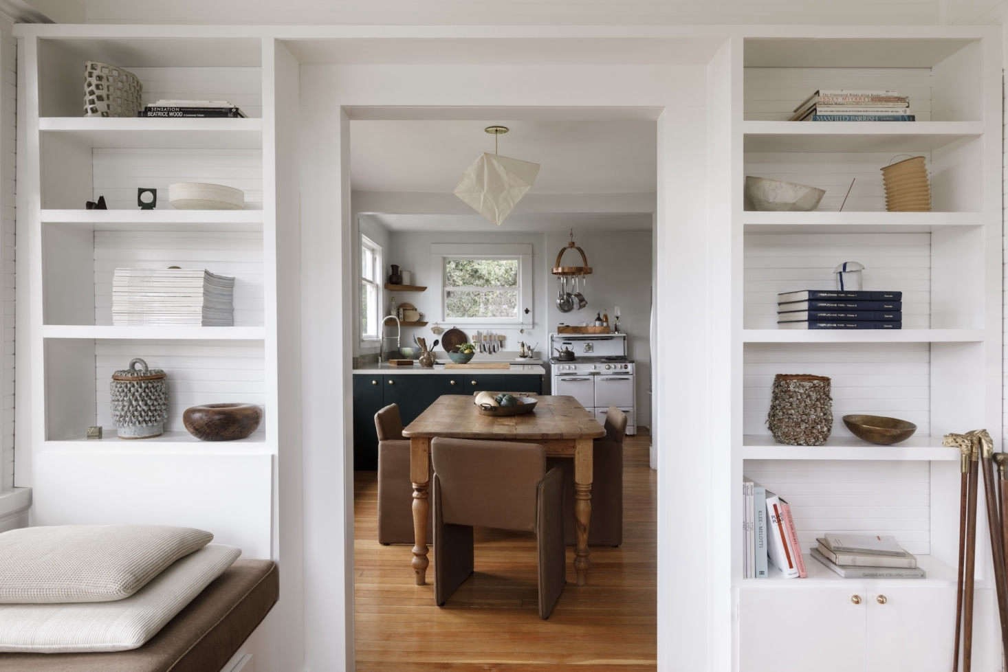 The view from the sunroom into the dining/kitchen space. The built-in shelves display works by some of her favorite ceramicists, includingDavid Korty,Victoria Morris,Morgan Peck, and Kelly Lamb. The collection of canes is a gift from Kathleen&#8
