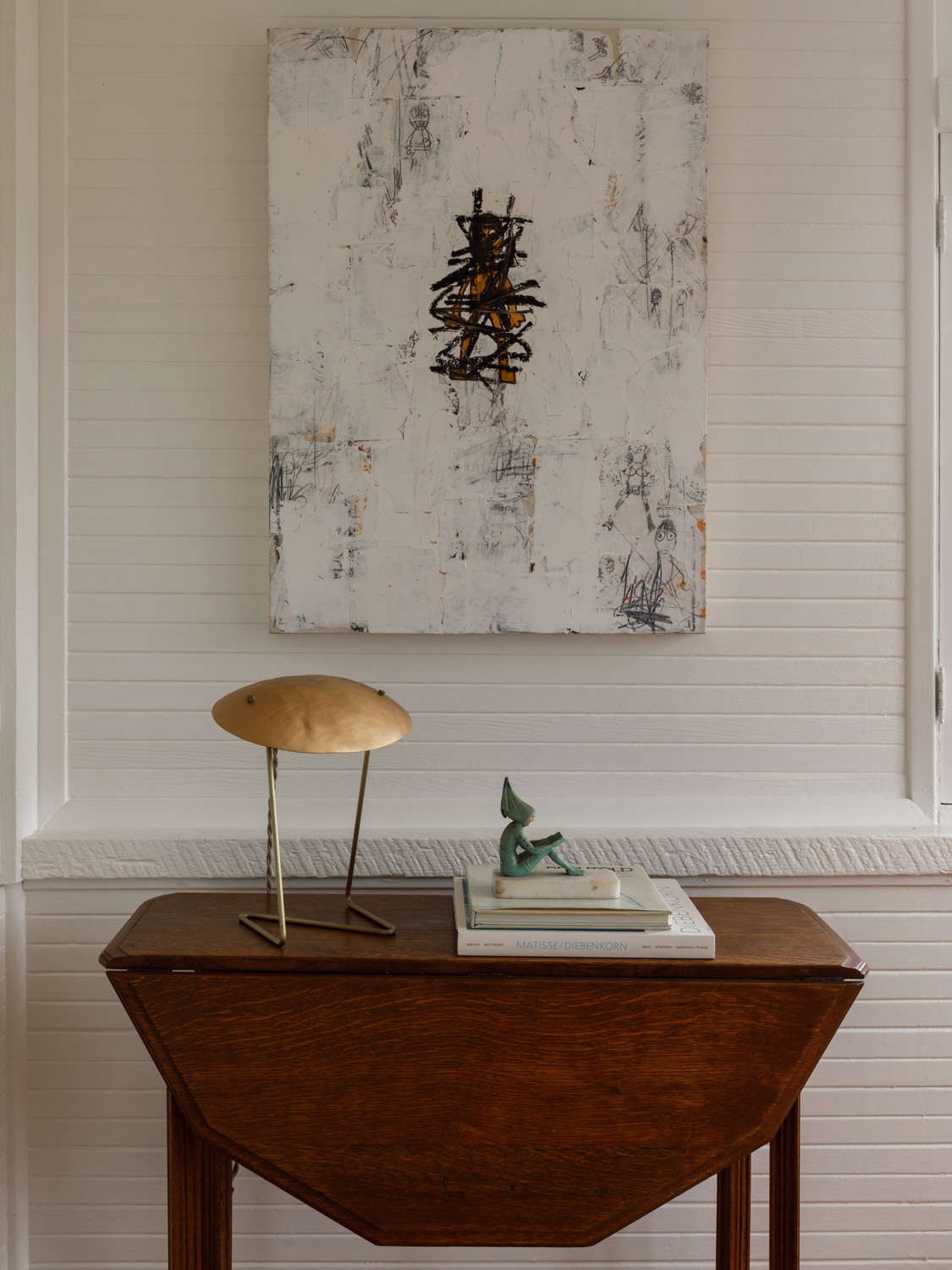 A Lindsey Adelman lamp rests under a painting by Jay Stuckey.