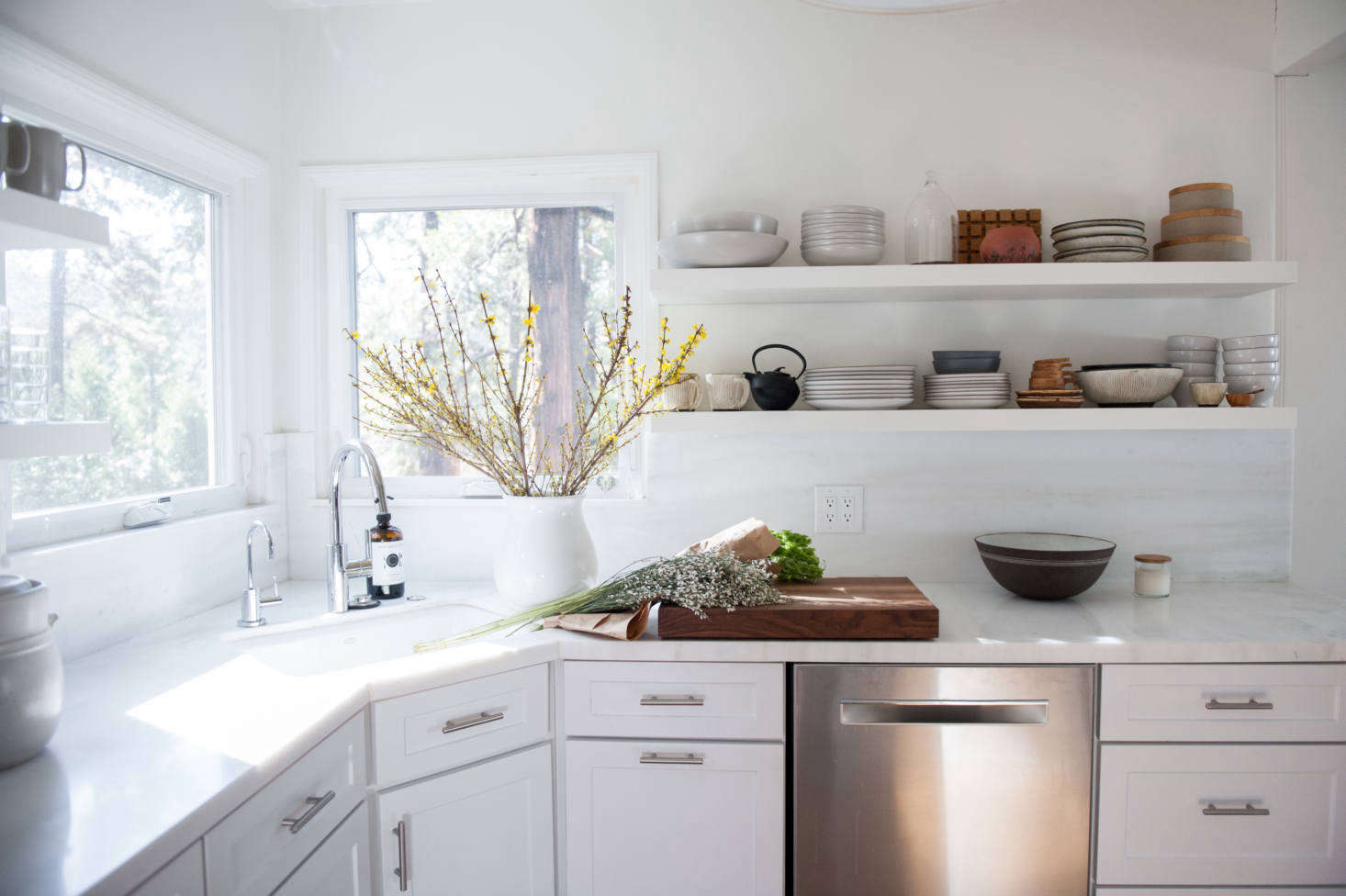 """The counter and backsplash are Pentelico, a marble with subtle greenish veining: """"It came polished and I had it honed, which feels more casual and better for the cabin,"""" says Lauren."""
