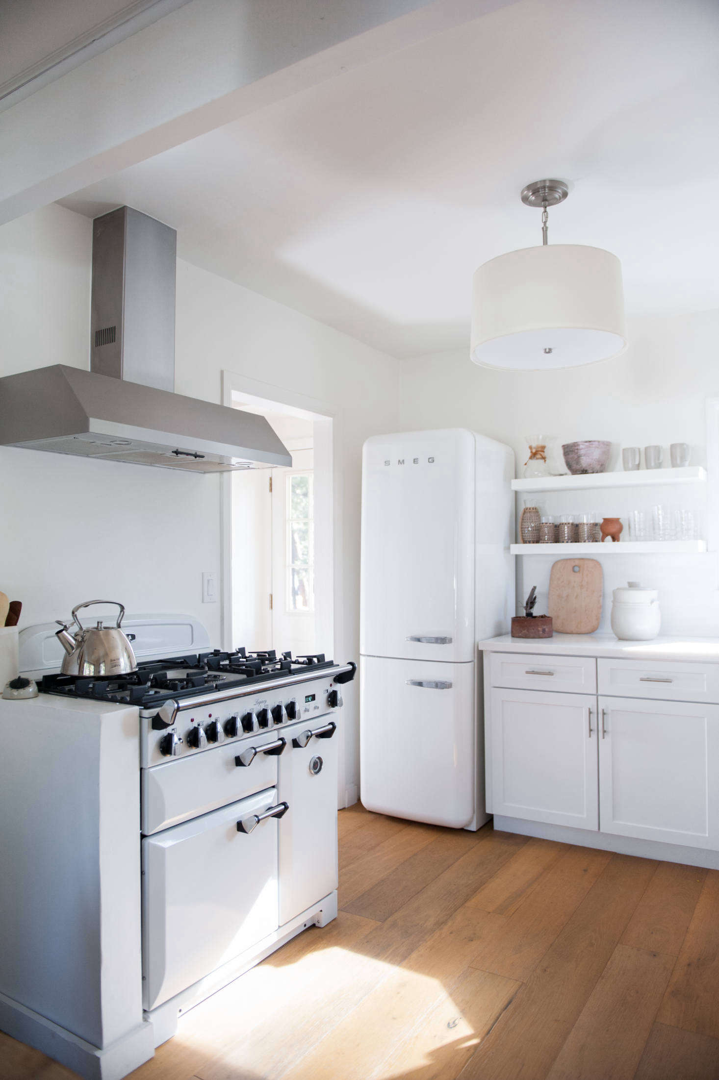 Wire-brushed, engineered wide-plank oak floorboards replaced the kitchen's wood laminate (as well as the living room and bedroom's wall-to-wall carpeting). The range is Aga's Three Oven gas model.