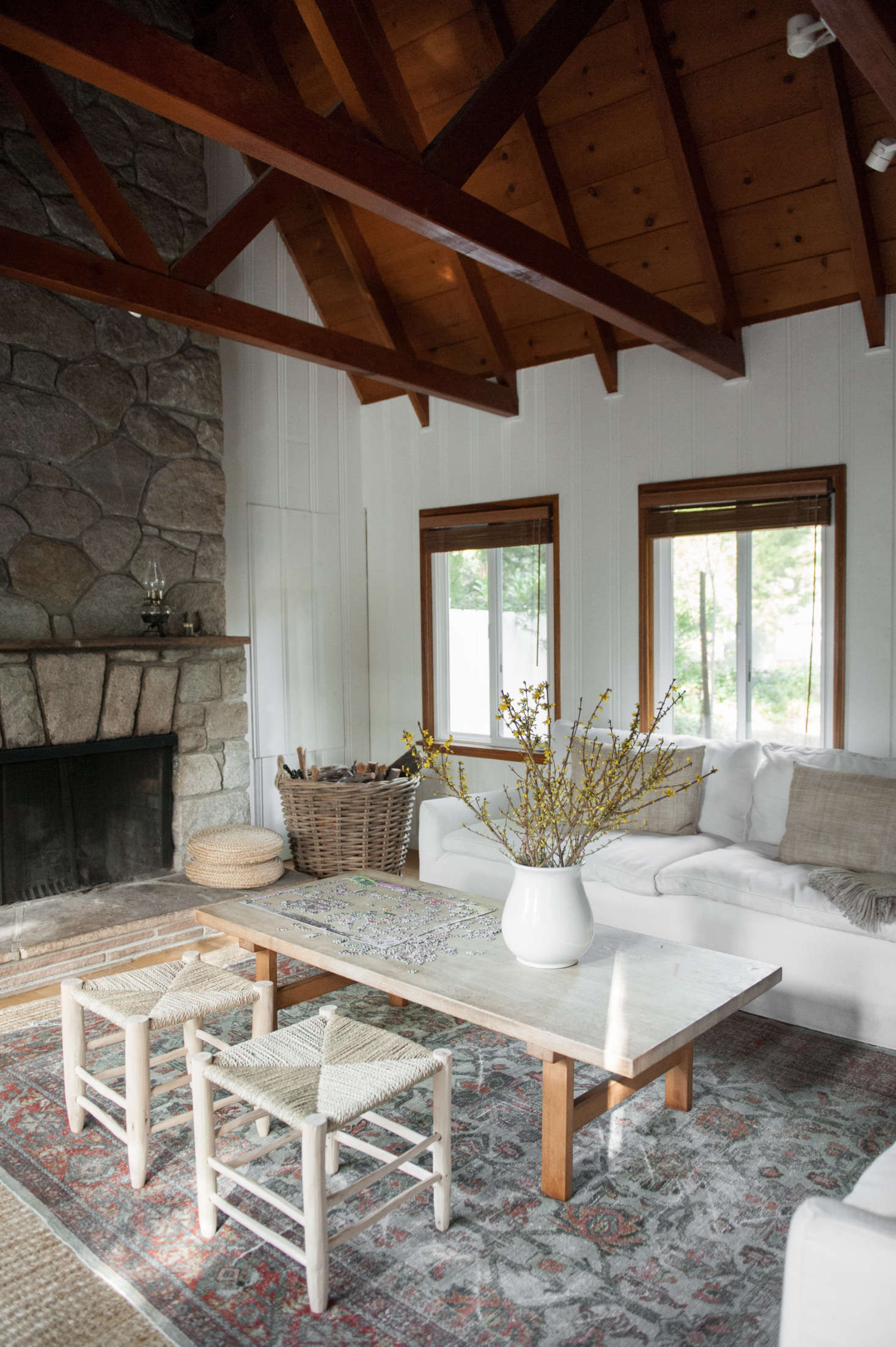 """The stone fireplace is original and gets put to use year-round. Lauren placed a patterned carpet over a sisal base: """"The layered look adds depth, and in the summer, just the sisal can be used."""""""