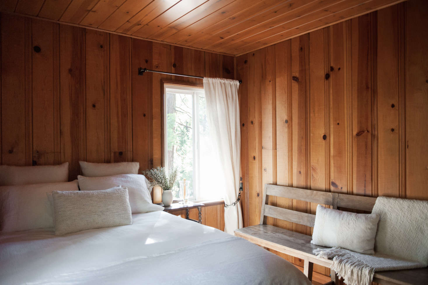 The paneling in the bedrooms was also left natural butsanded to mute its varnished finish. Shown here: the first floor guest room.