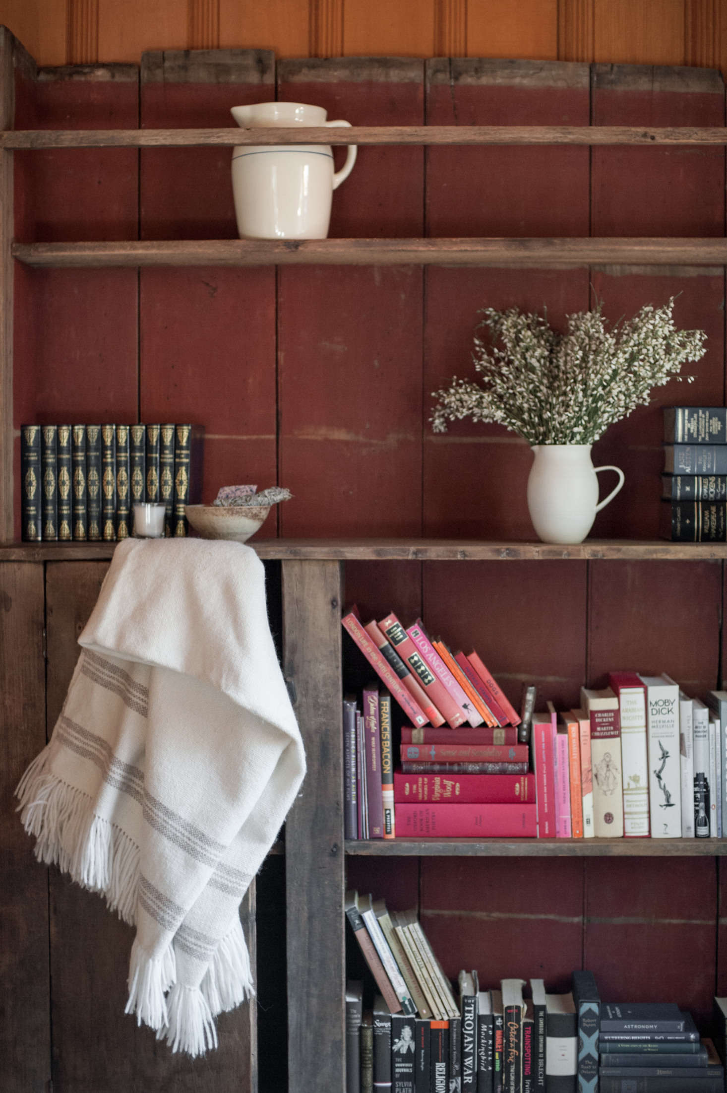 In the guest room, a painted bookcase found at Brenda Antin Antiques holds Leanne's late mother's books.