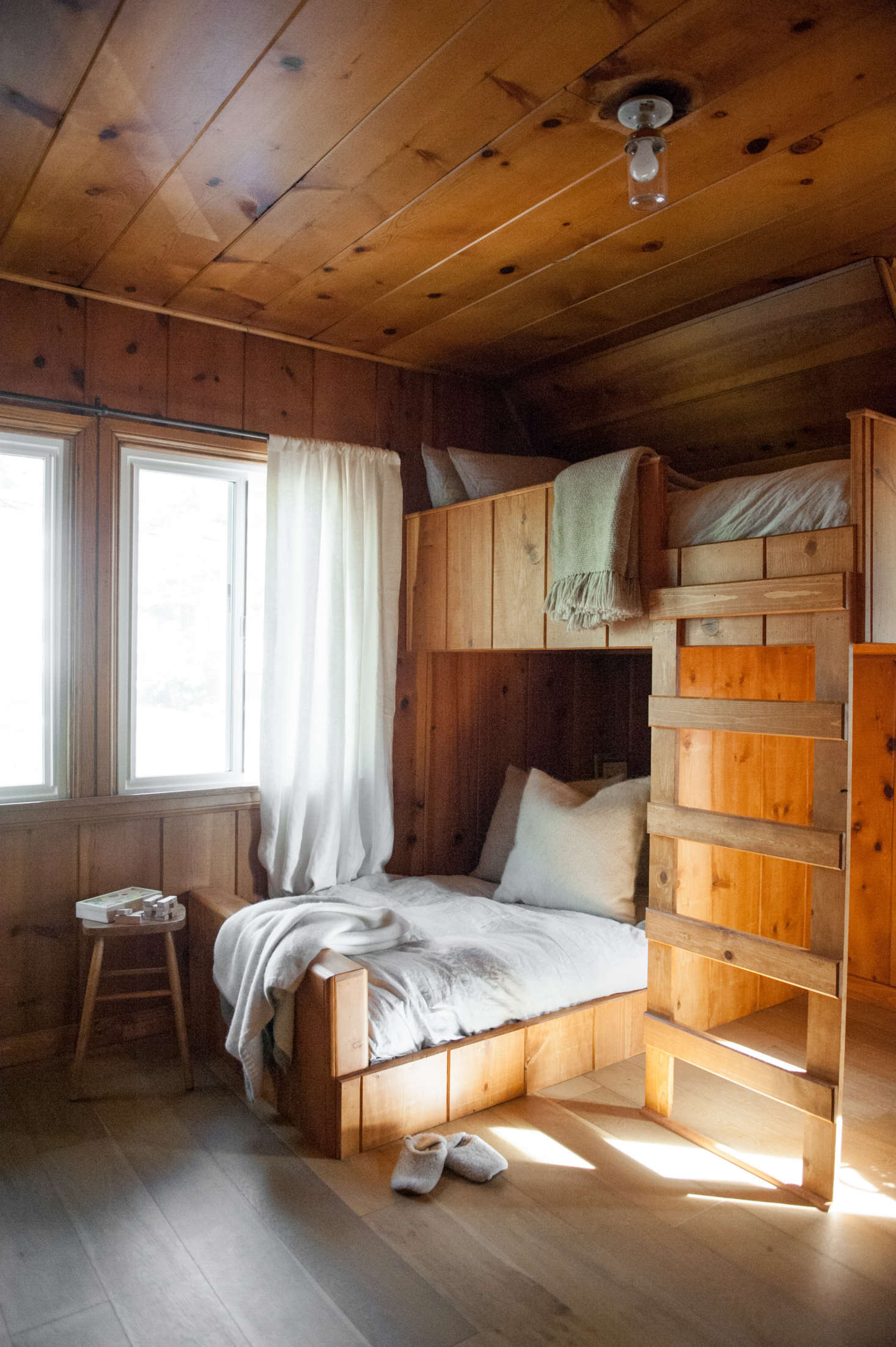 """Lauren designed the custom bunk beds to continue the lines of the existing paneling.""""The staggered configuration of bunks creates some space underneath,"""" she says. """"The setup works with the shape of the room and was inspired by images of Scandinavian cabins and ski chalets."""""""