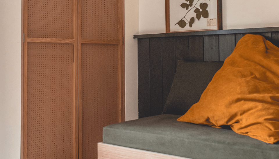 A detail of the hotel's rust-and-sage palette and framed botanicals.