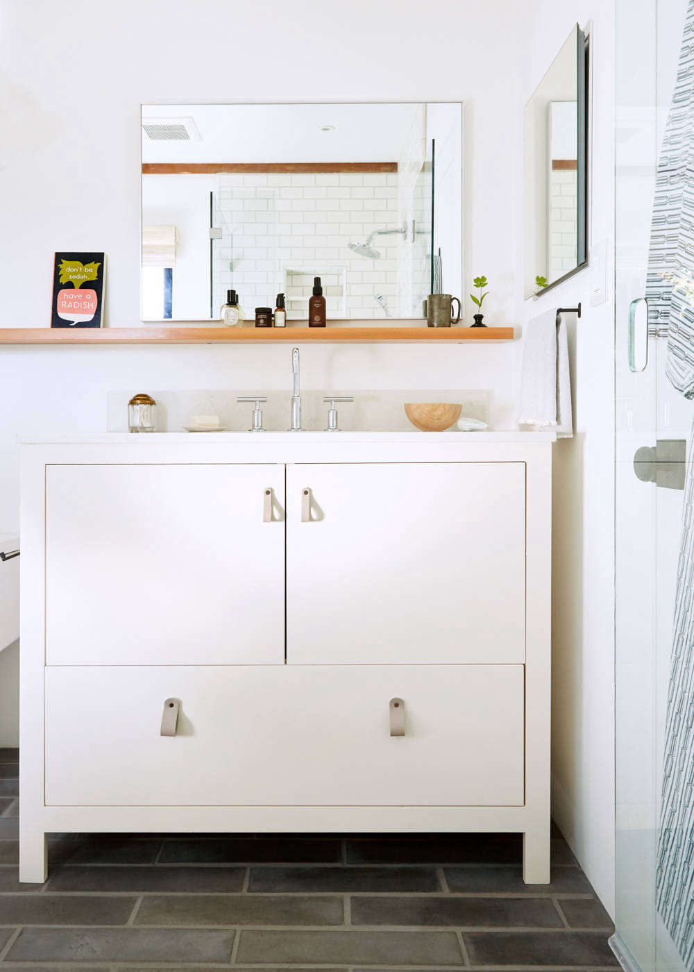 """Look closely and you'll see that the shower door has an oval cutout pull: """"The space between the vanity and shower door is not terribly wide, so I spec'd a cutout in the glass to avoid a protruding handle."""" The sink console was made by Alfredo Garcia of H & H Cabinet in Oakland and painted in Farrow & Ball Dimity. The gray leather looppulls are from 3 Twenty Leatherworks, and the sink fixtures areKohler Purist in polished chrome. The sink counter is IRG Pental Quartz in Lattice. The24-by-36-inch Infinity Mirror mounted over the sink is from CB2."""