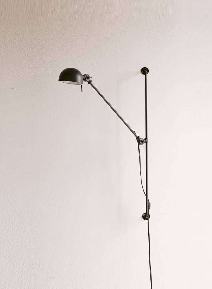 "The Simon Adjustable Sconce, also made of black steel and ""inspired by modern industrial design,"" shares a similar structure: an articulated arm mounted on a fixed vertical rod. It's $89 from Urban Outfitters."