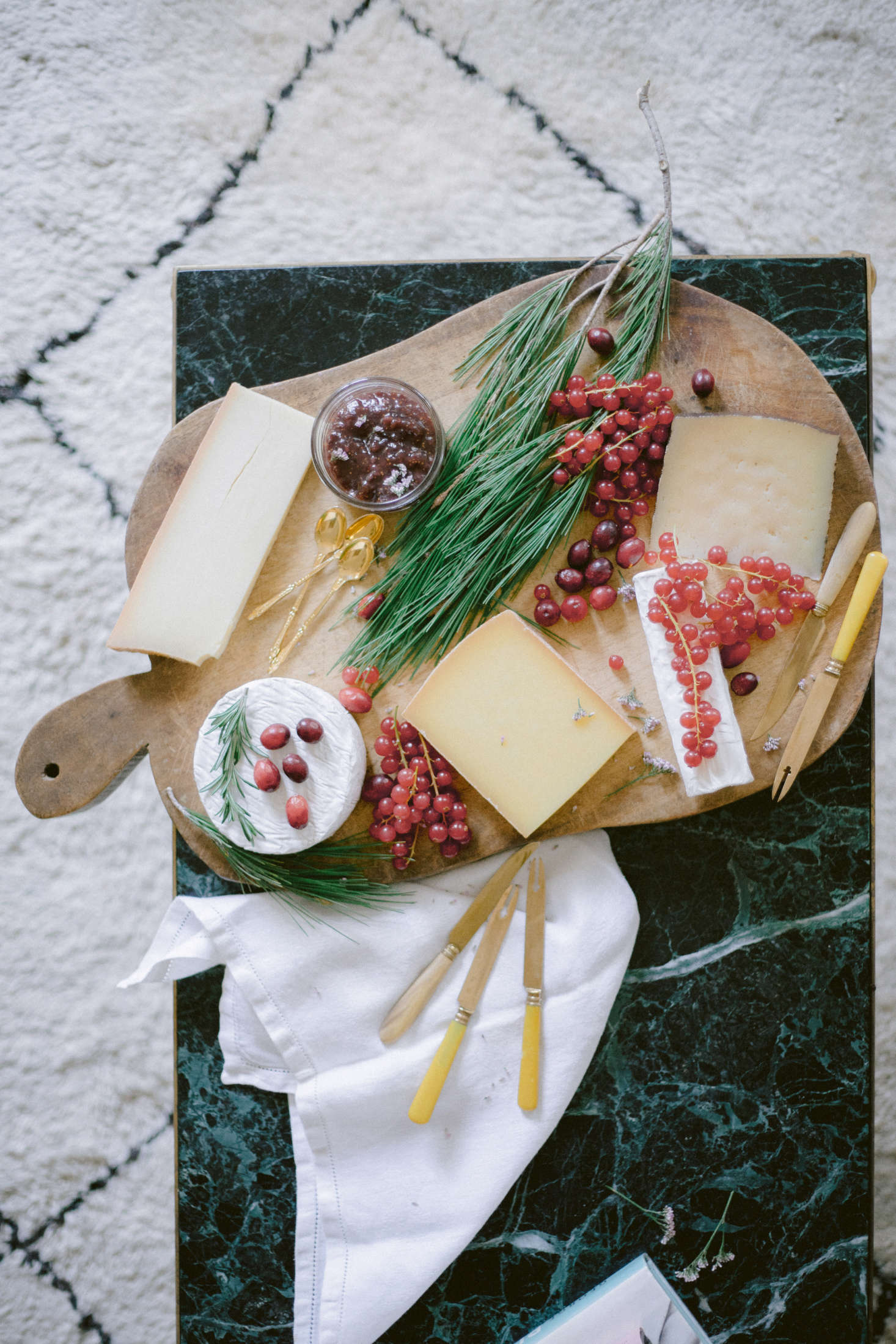 Tiny pink berries and greens add liveliness to the cheese board.