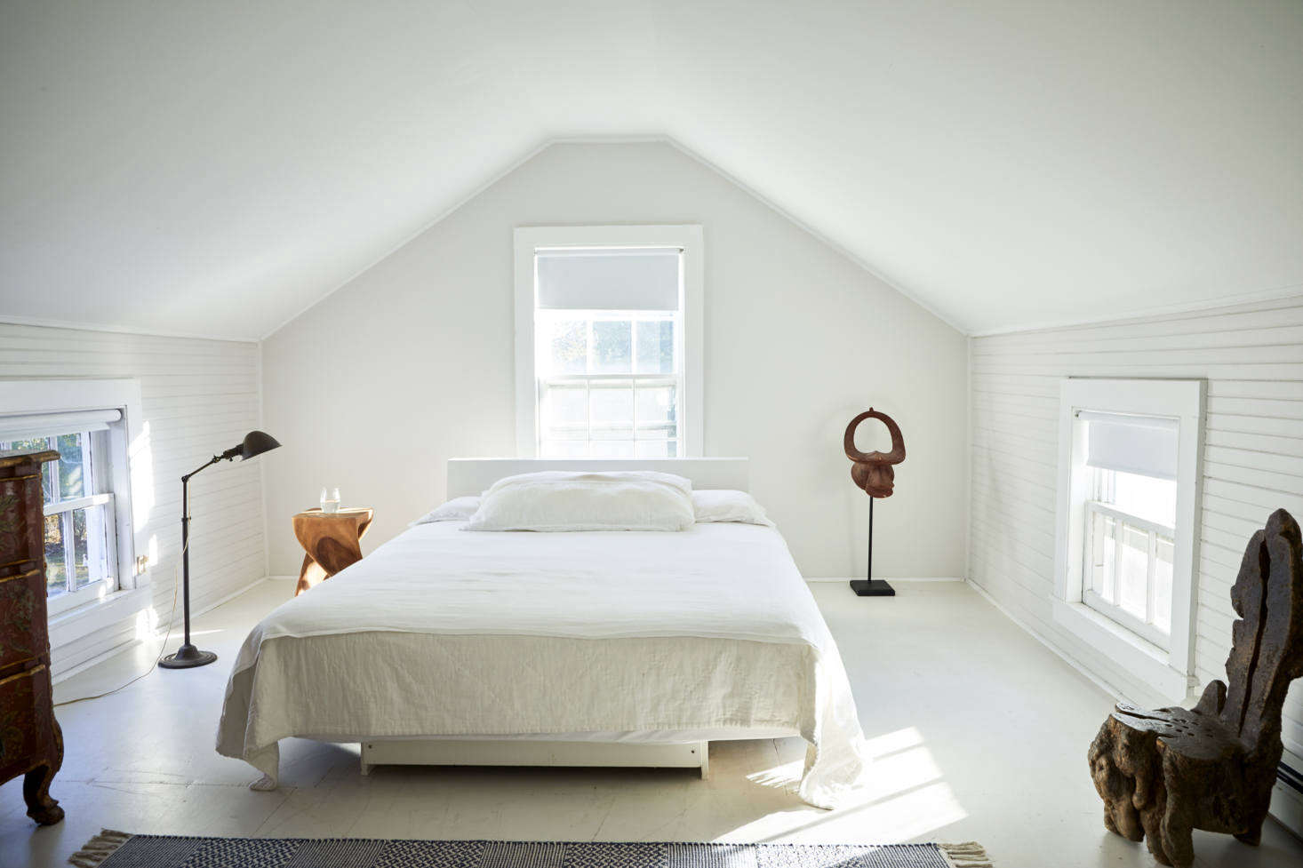 Set under the eaves, the master bedroom has a platform bed that Jonathan built from wood left over from the library shelves. It overlooks a large soaking tub at the other end of the room.