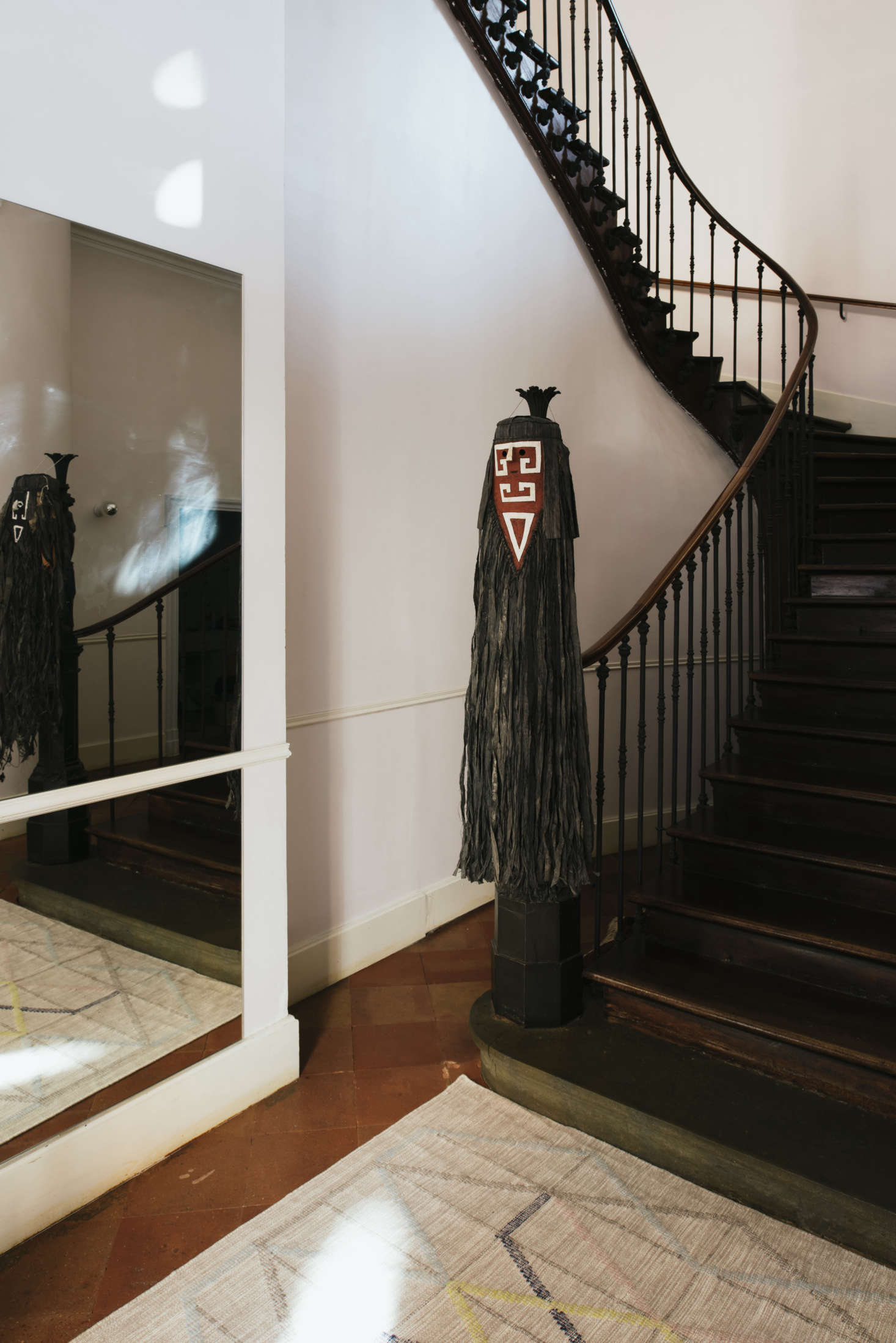 """Hanging from the banister is a Tamok mask. """"They come from Amazonia, Guyana, made by the Wayana,"""" Sathal says. """"It was Christophe who brought them back after a trip to Guyana, because he is a director and wrote a play with a young Wayana woman."""""""