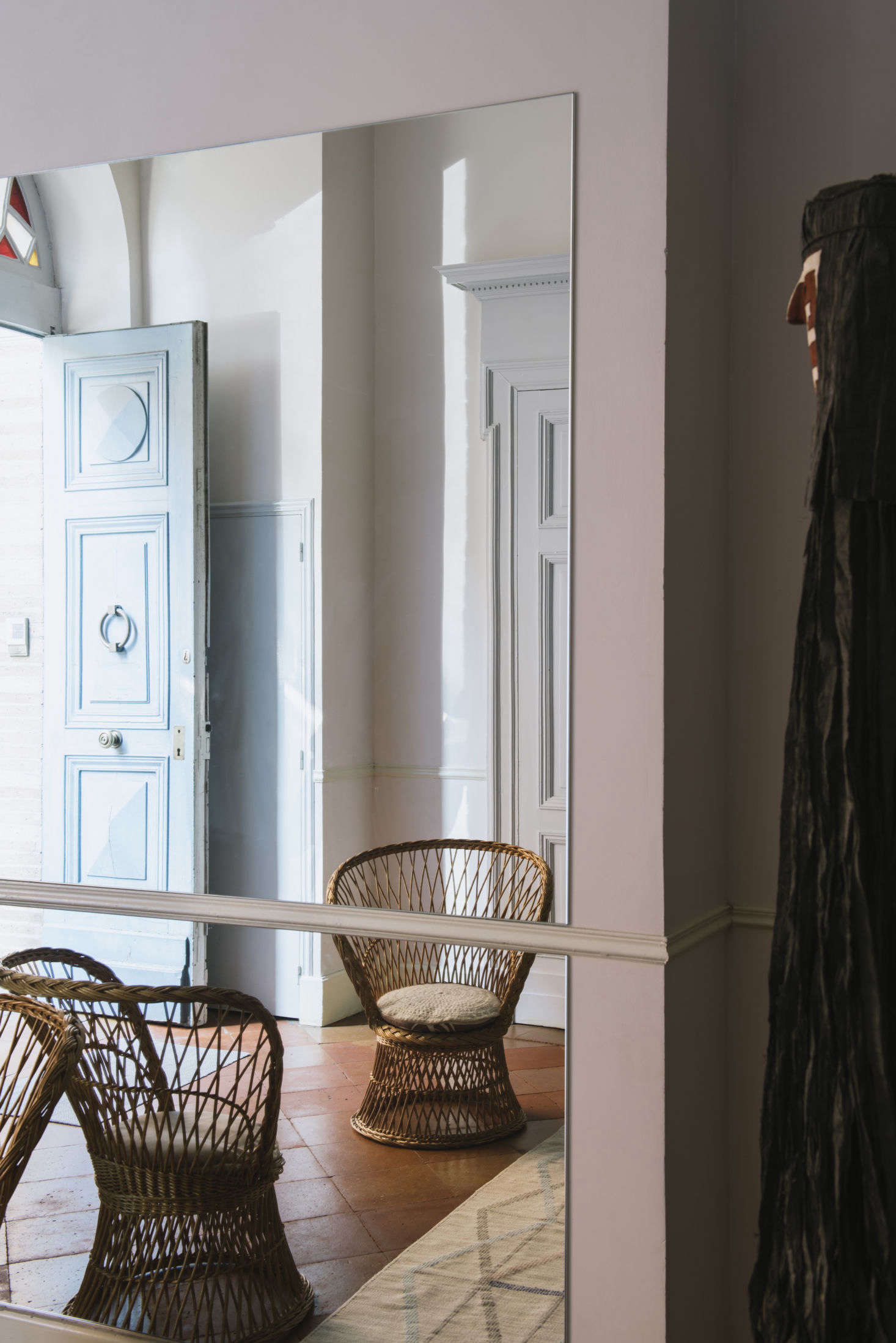 Stepping into the house, entrants are greeted by a cheerful blue door, a rattan chair, and panels of mirrors.